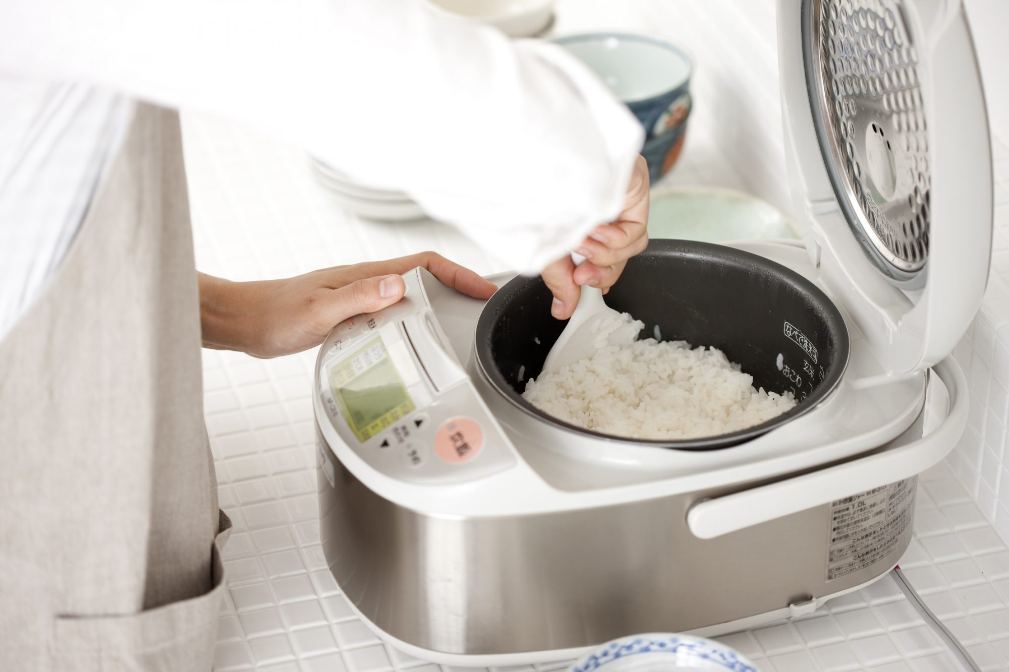 woman scooping rice from a rice cooker