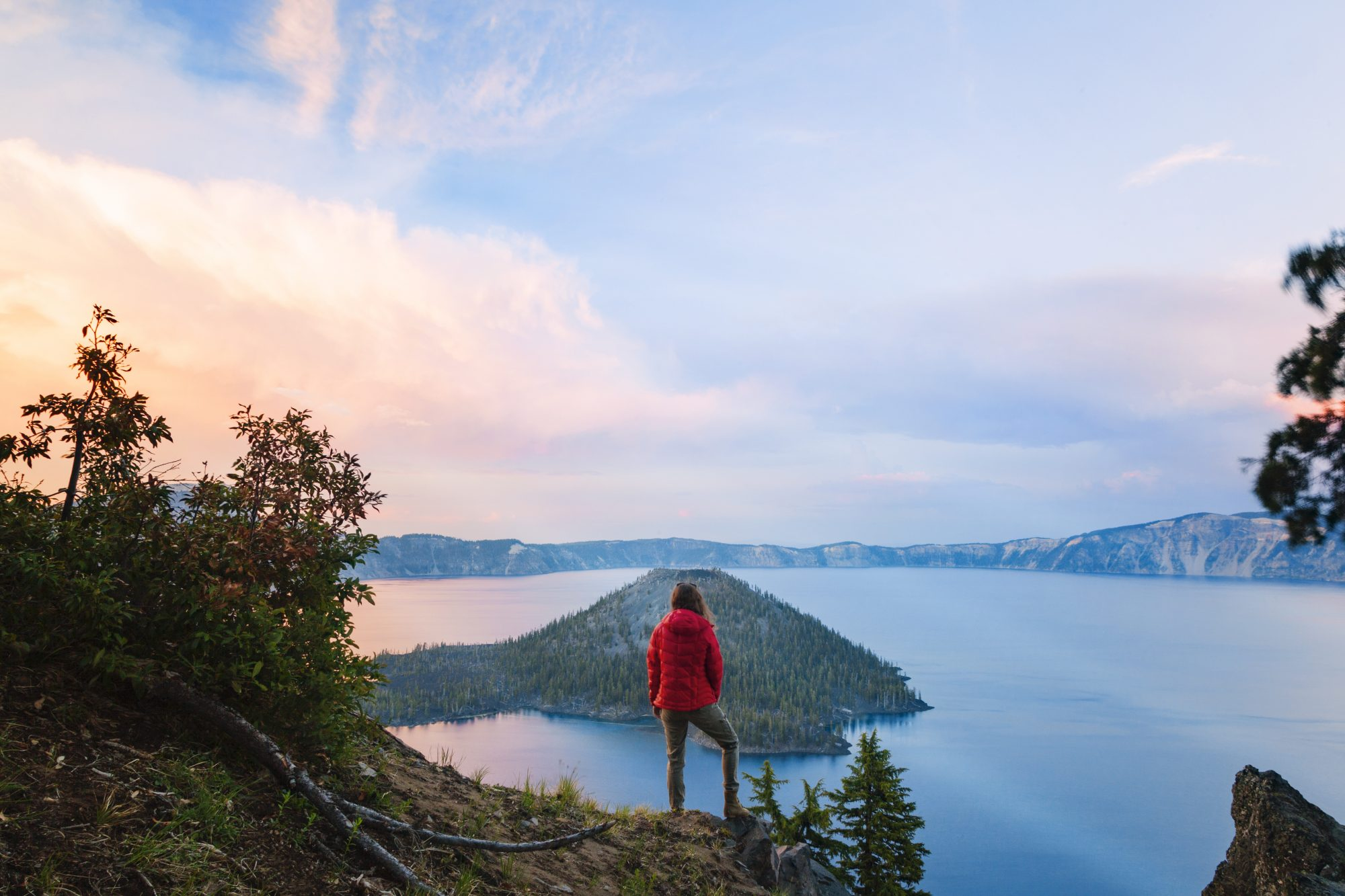 Rear view of woman standing on cliff against Crater Lake