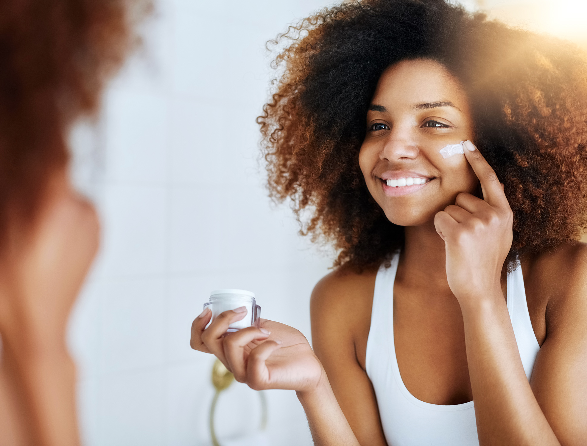 young woman applying moisturizer to her face in front of the mirror
