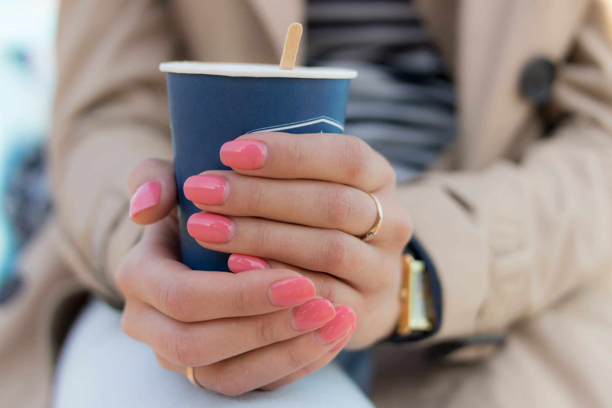 woman holding coffee cup with pink manicure