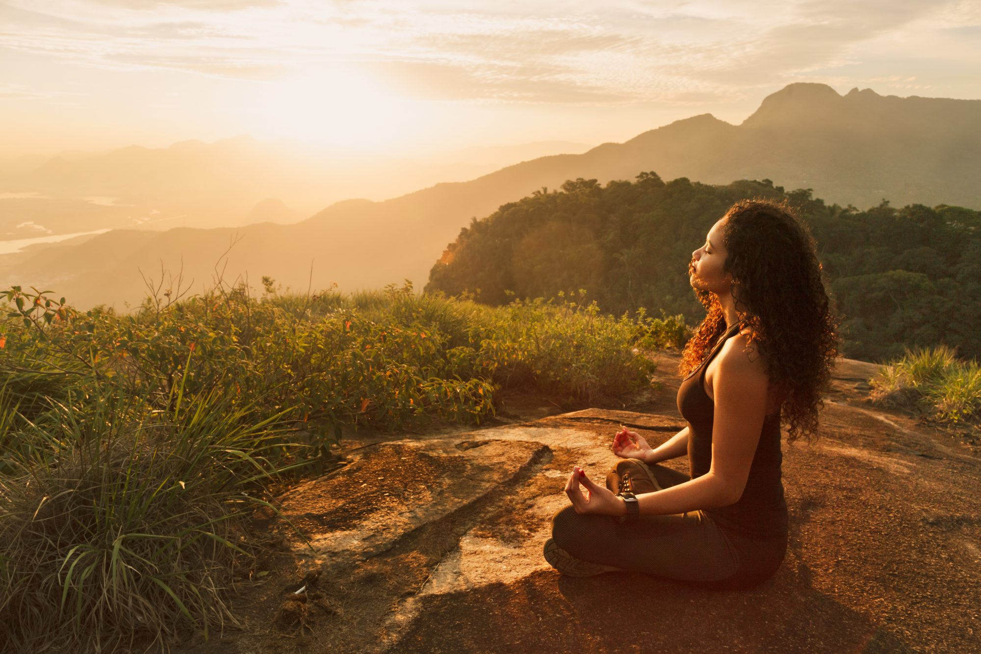 woman meditating on mountain as sun sets