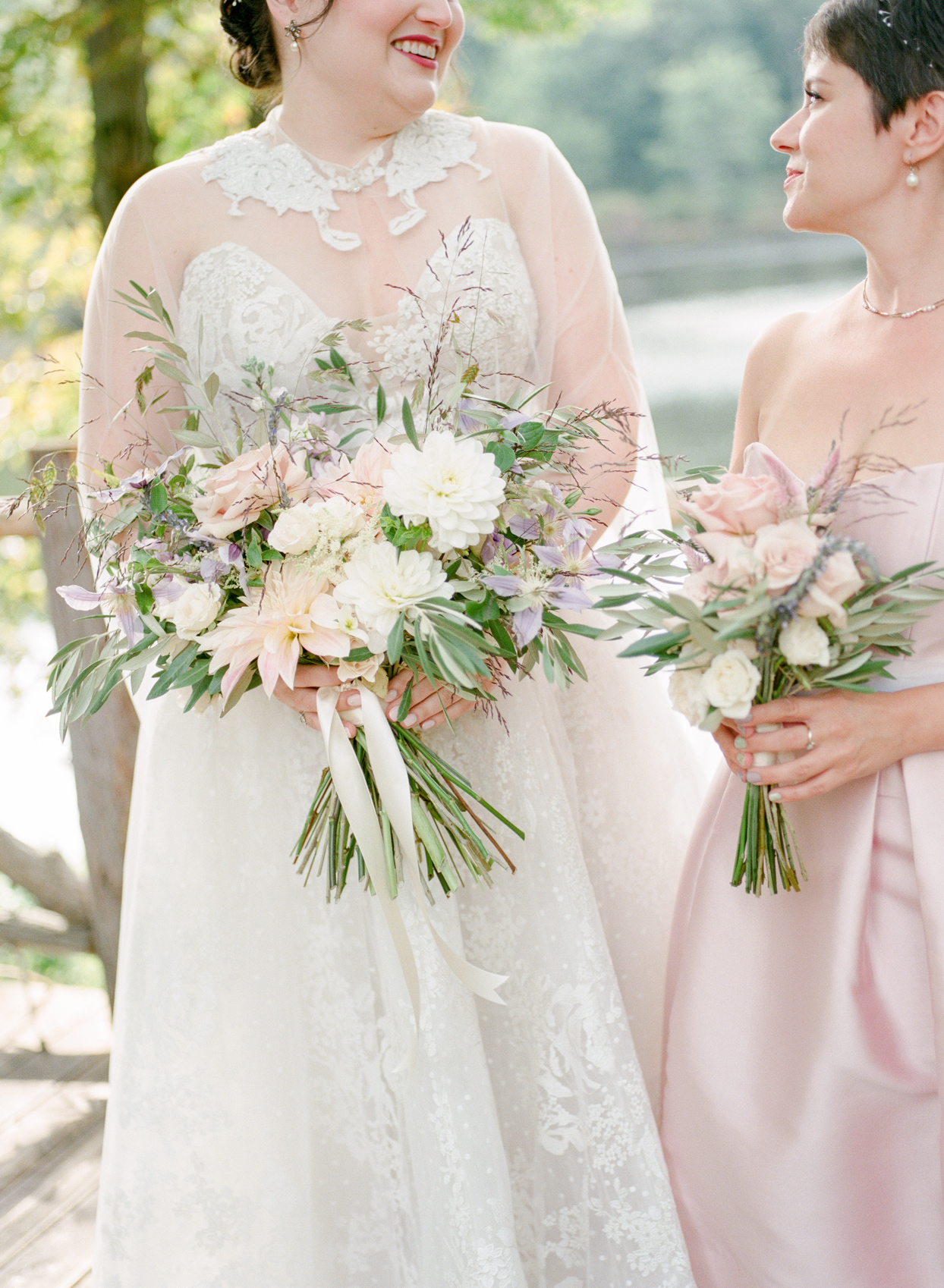 bride and maid of honor holding bouquets of roses and lavender