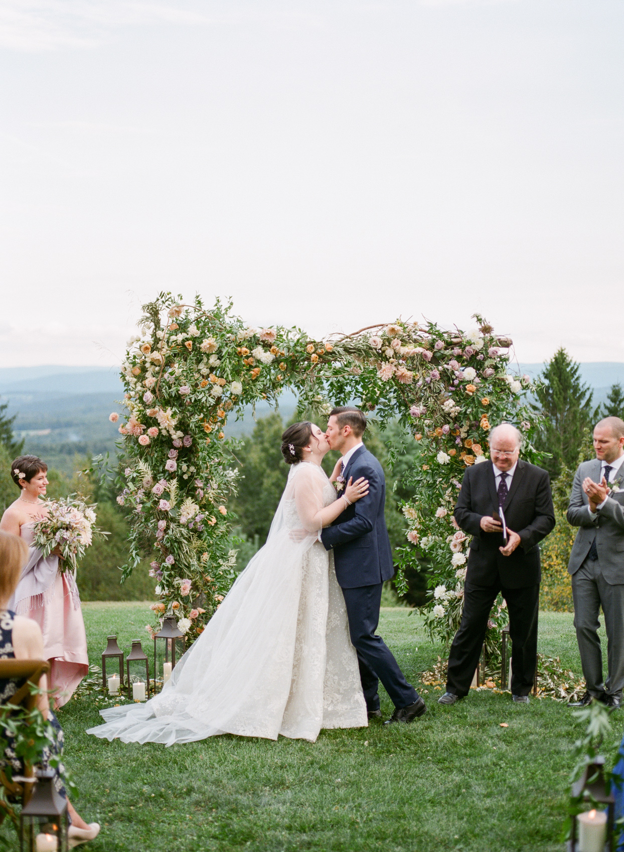 bride and groom kissing beneath floral ceremony arch