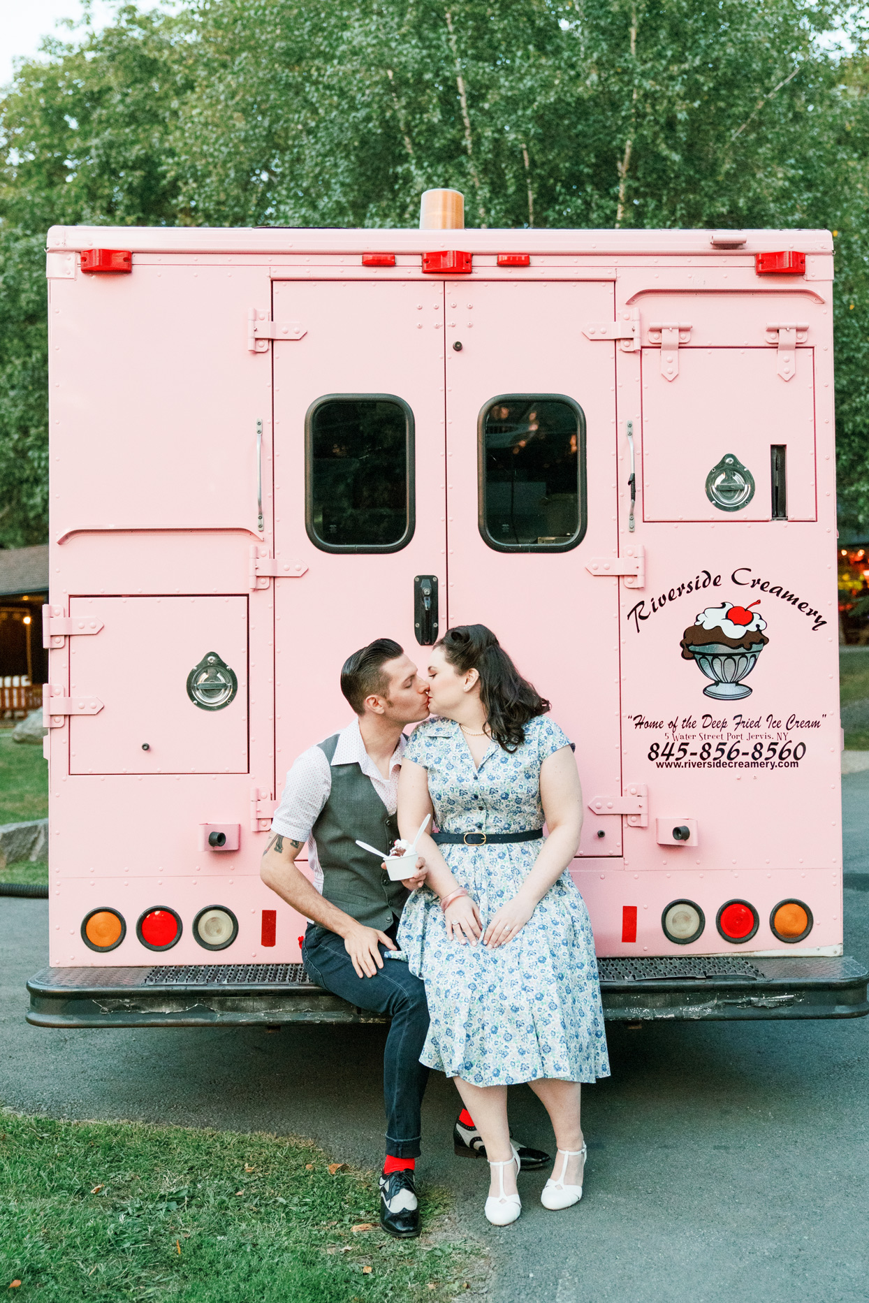 couple wearing vintage attire kissing behind ice cream truck