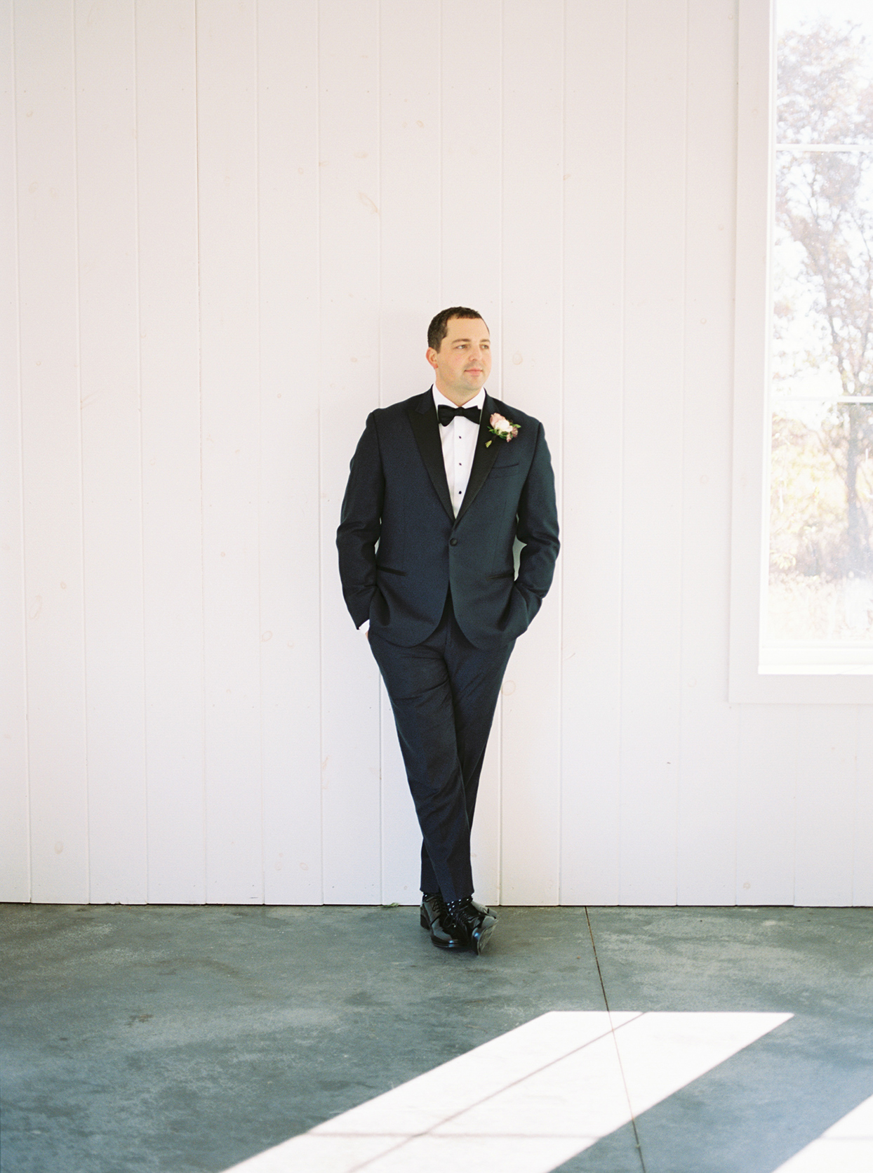 Groom in tux from The Black Tux in midnight blue with black lapels