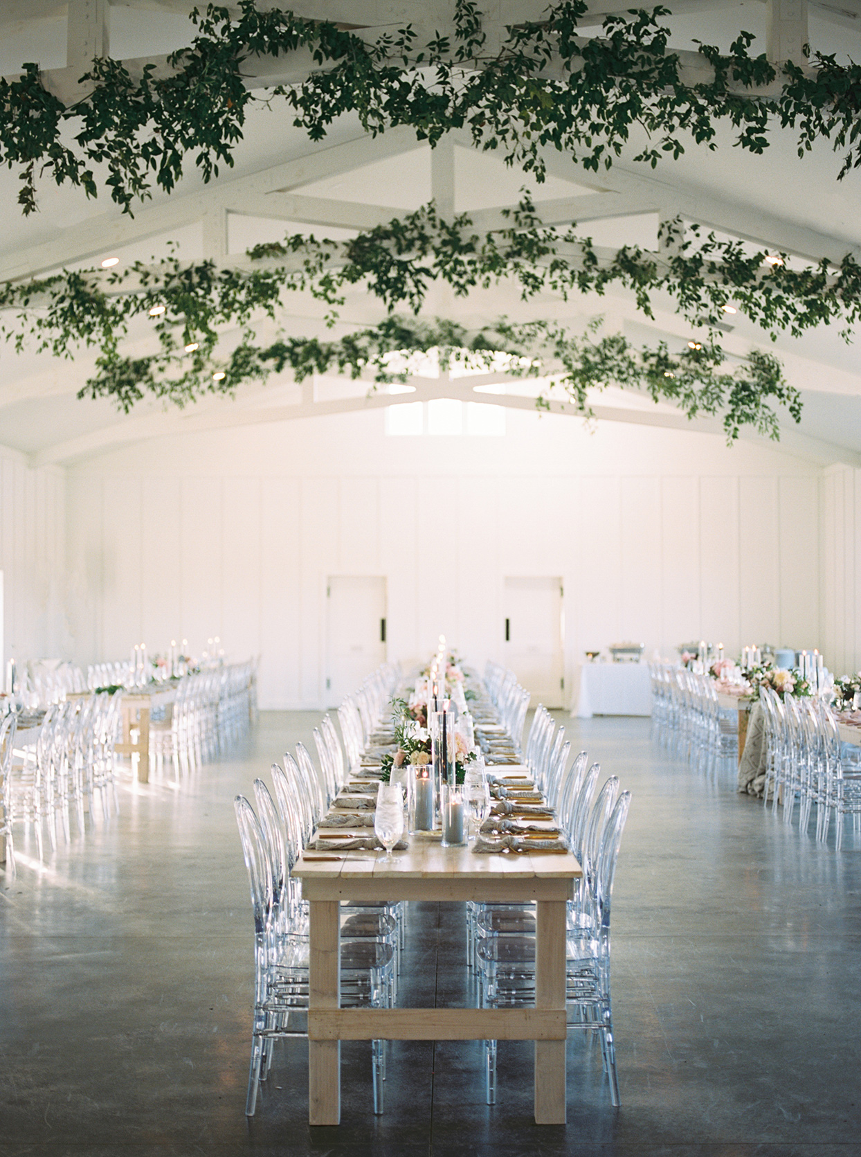 Wedding reception with long, natural wood farm tables and acrylic chairs
