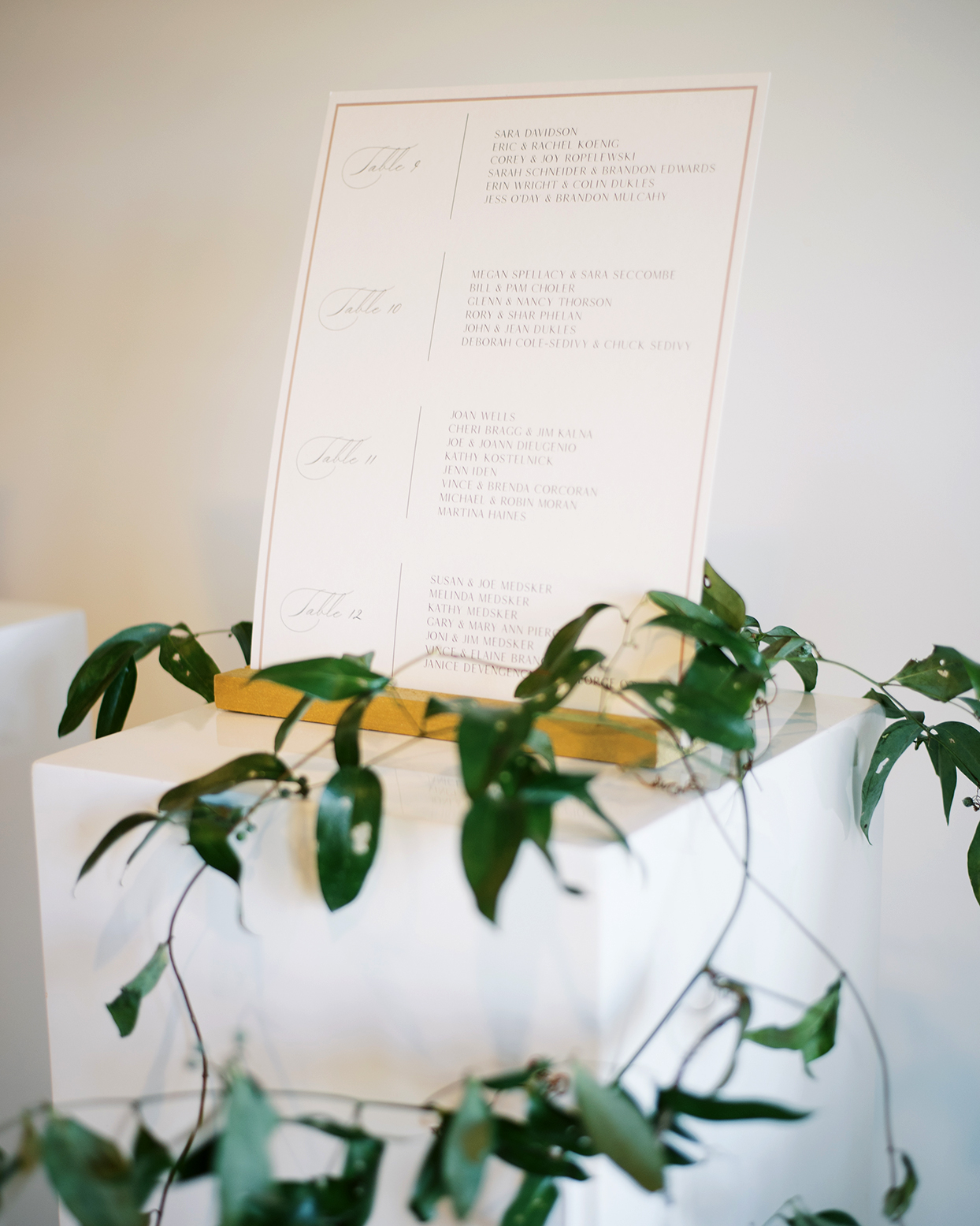 Guest table assignments on white columns draped in dark green leaves and flowing vines