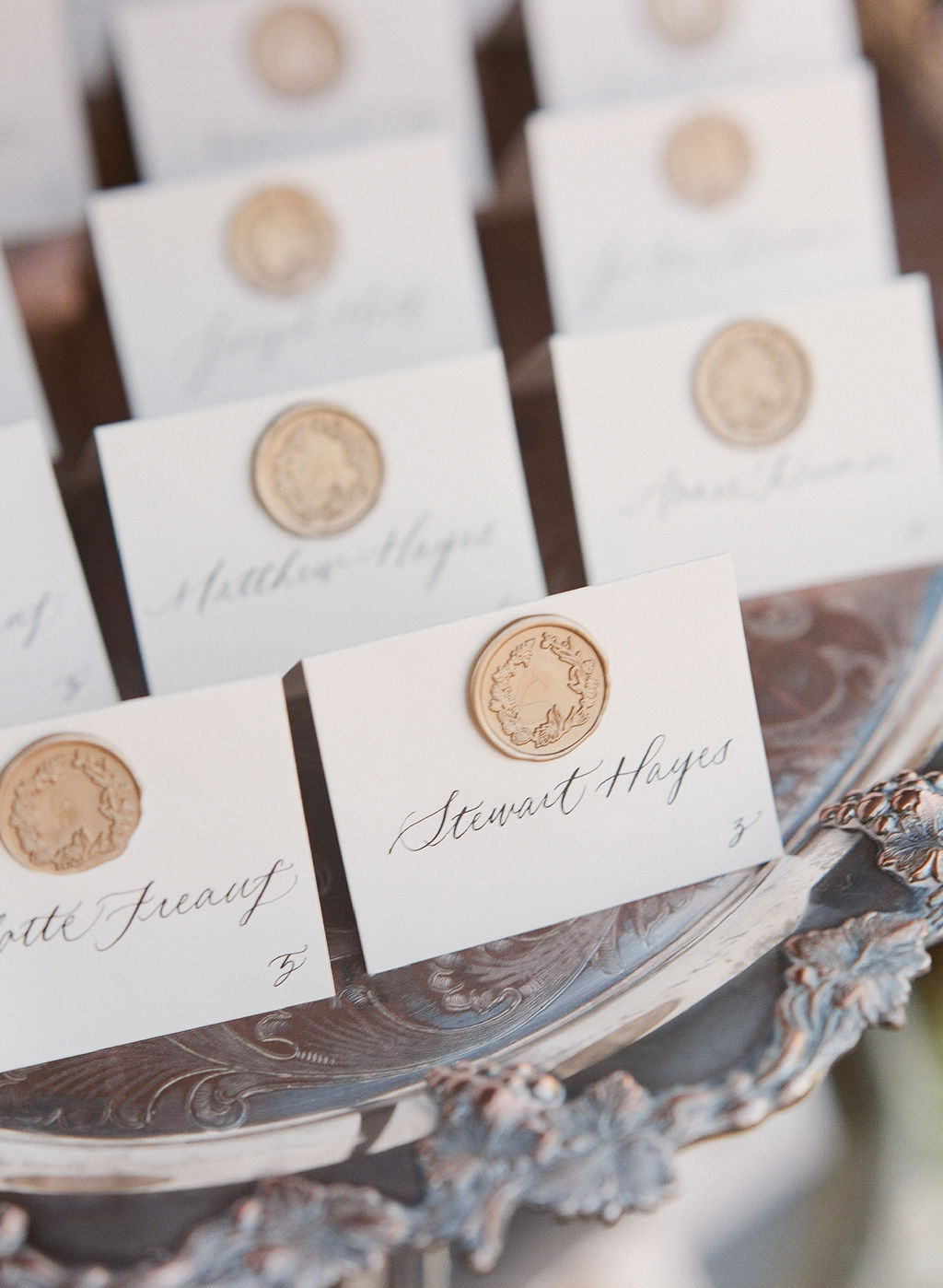 tented escort cards embellished with a gold wax seal