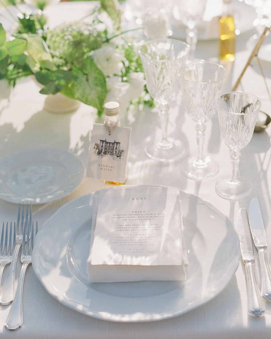 monochrome place settings with miniature bottles of olive oil as place cards