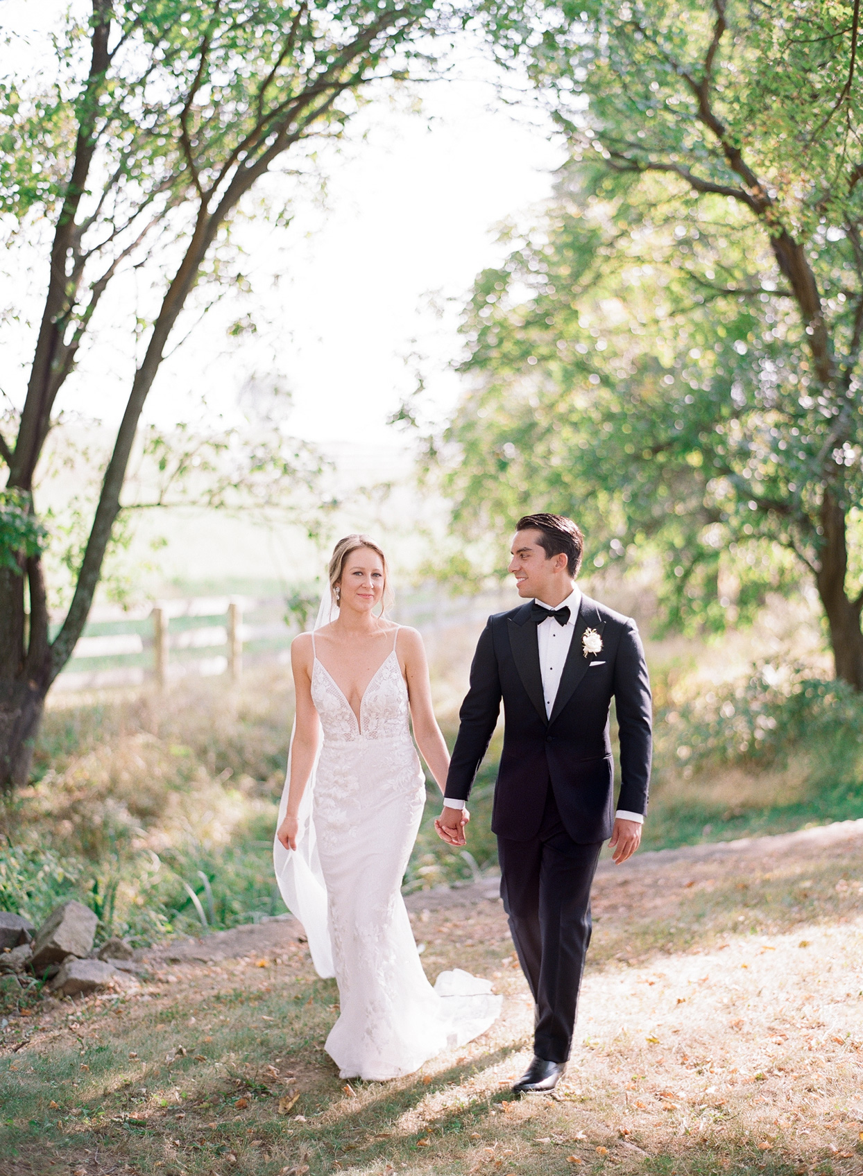 bride and groom holding hands walking in the grass under trees