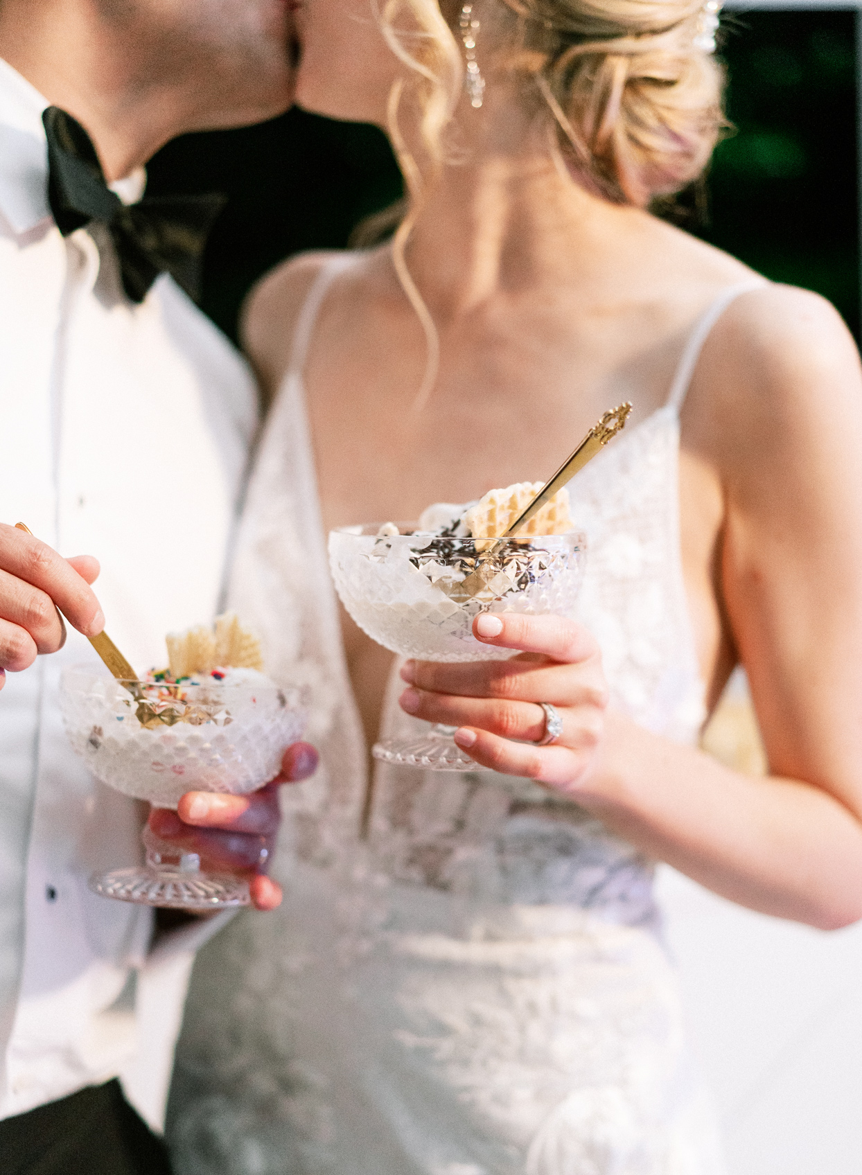 bride and groom share a kiss holding ice cream sundaes