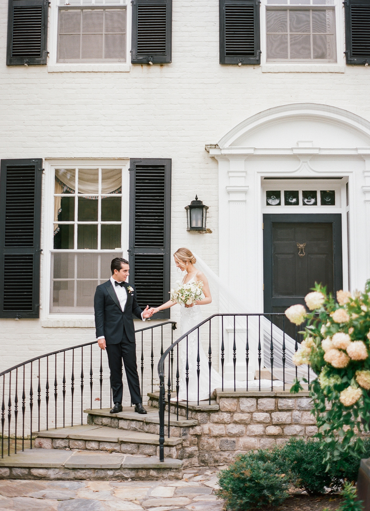 bride and groom standing outside on stone stairs during first look
