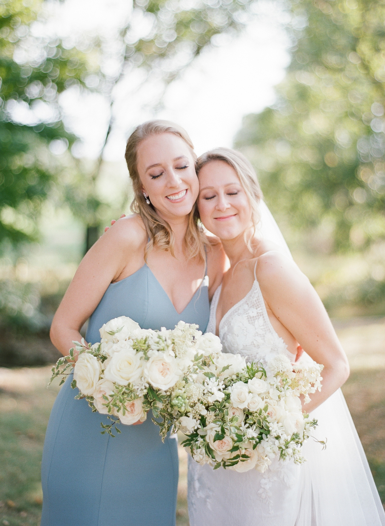 bride smiling with maid of honor wearing pale blue dress
