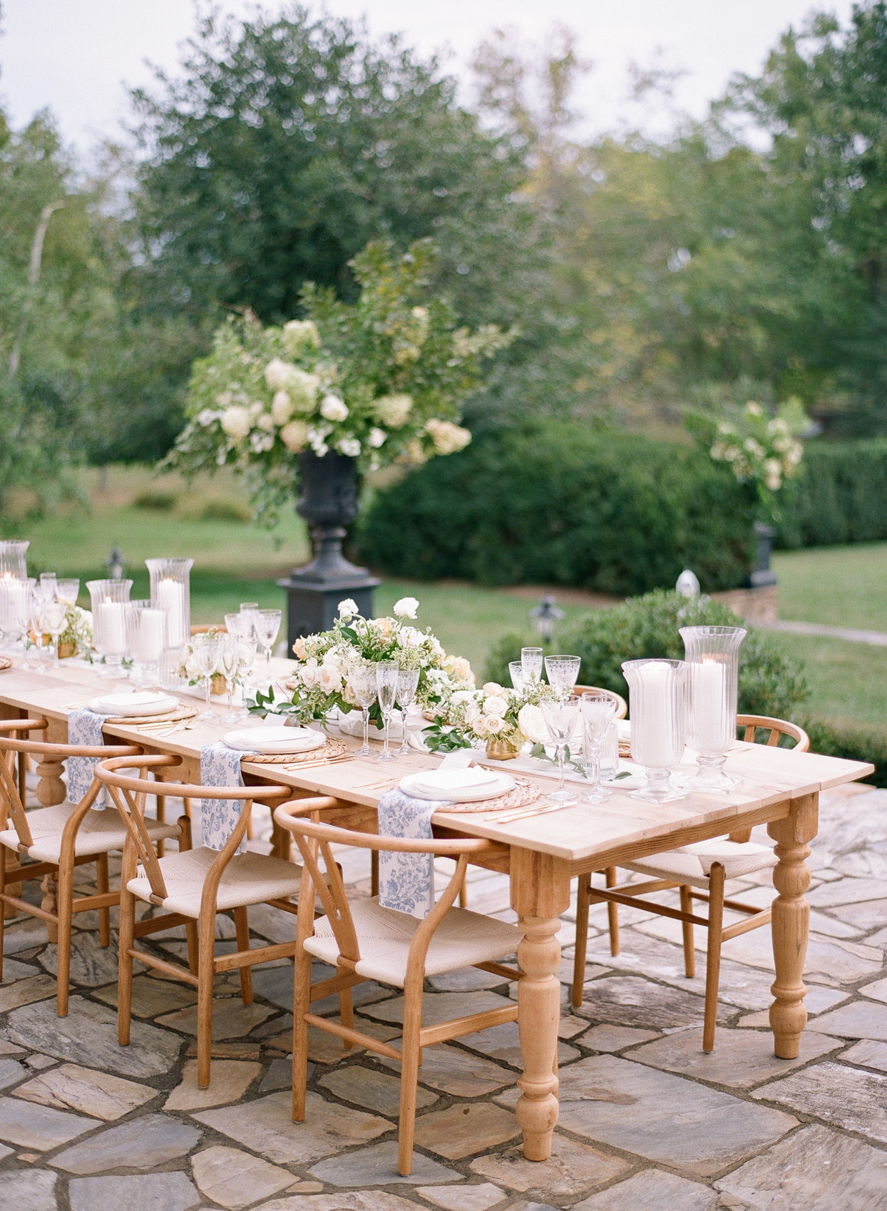 long wooden reception table with low white floral centerpieces