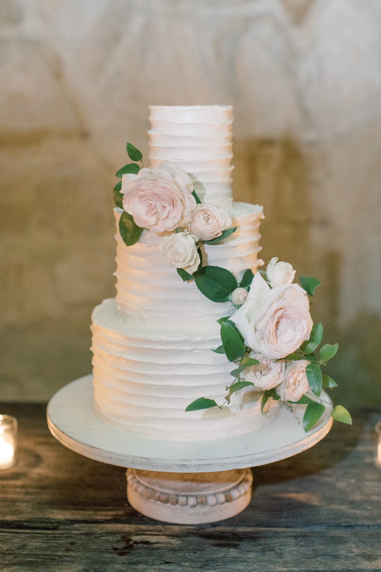 three-tiered wedding cake with floral accent