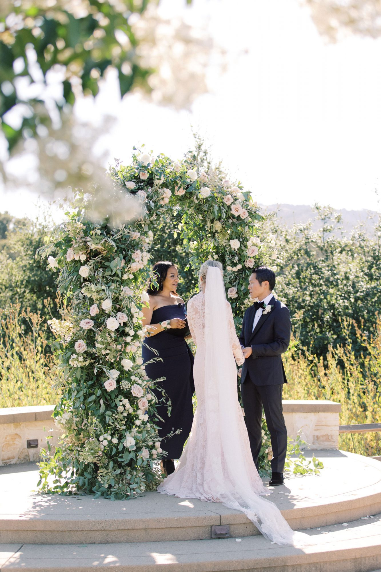 brider and groom in front of floral arch during ceremony