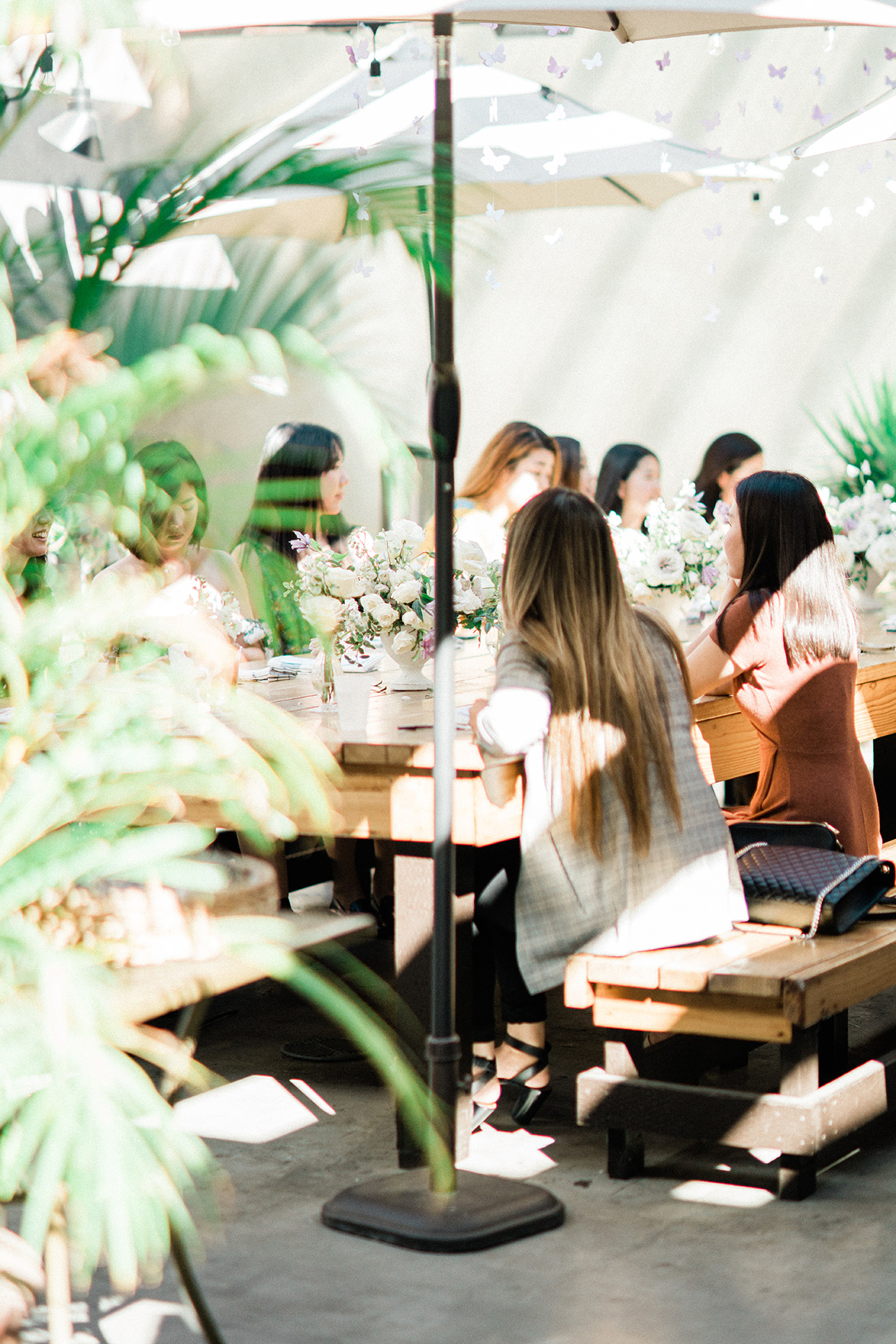 sally bridal shower sunlit tables with greenery, flowers, and umbrellas