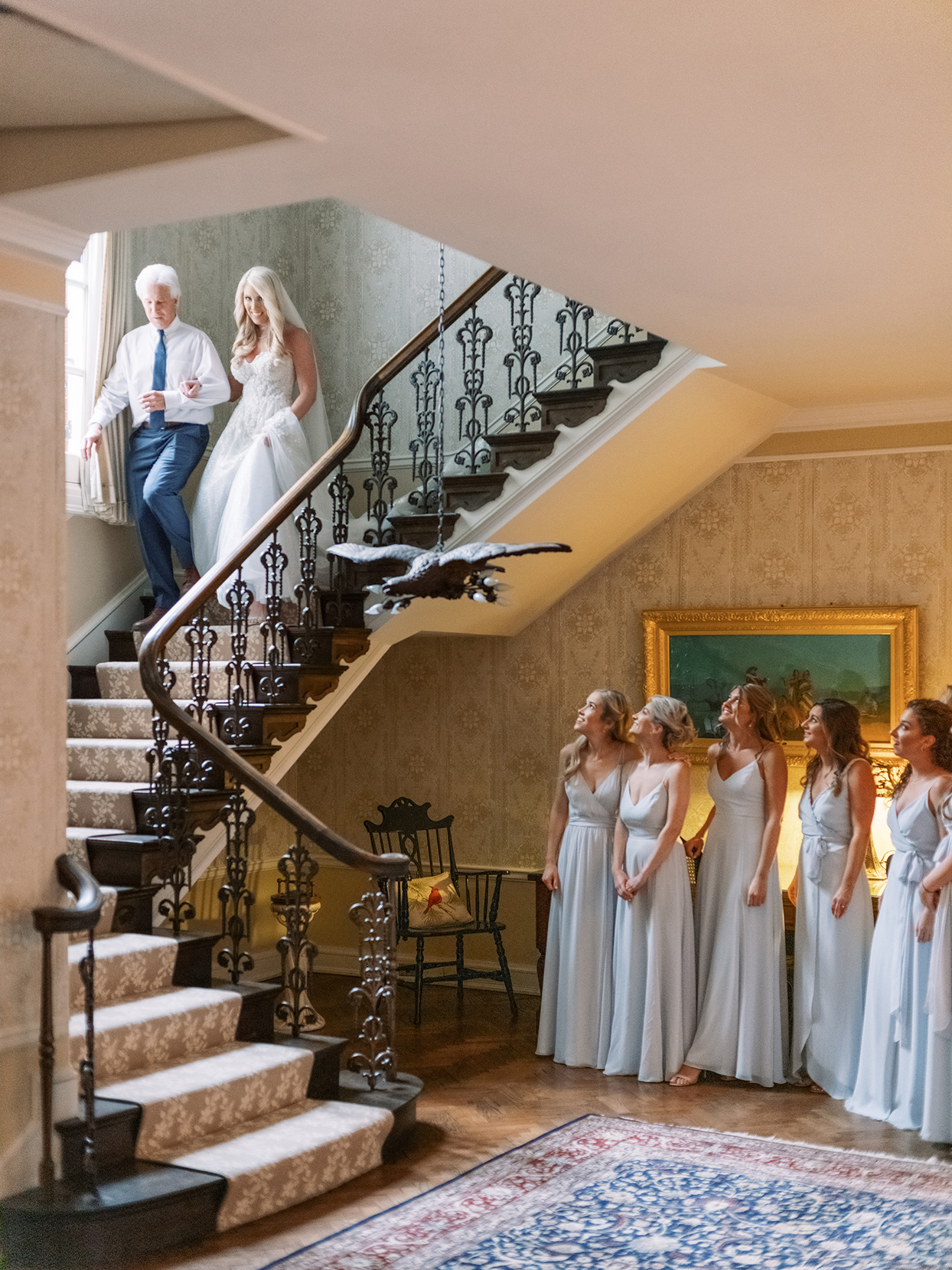 lauren chris wedding bride walking downstairs with father with bridesmaids waiting below