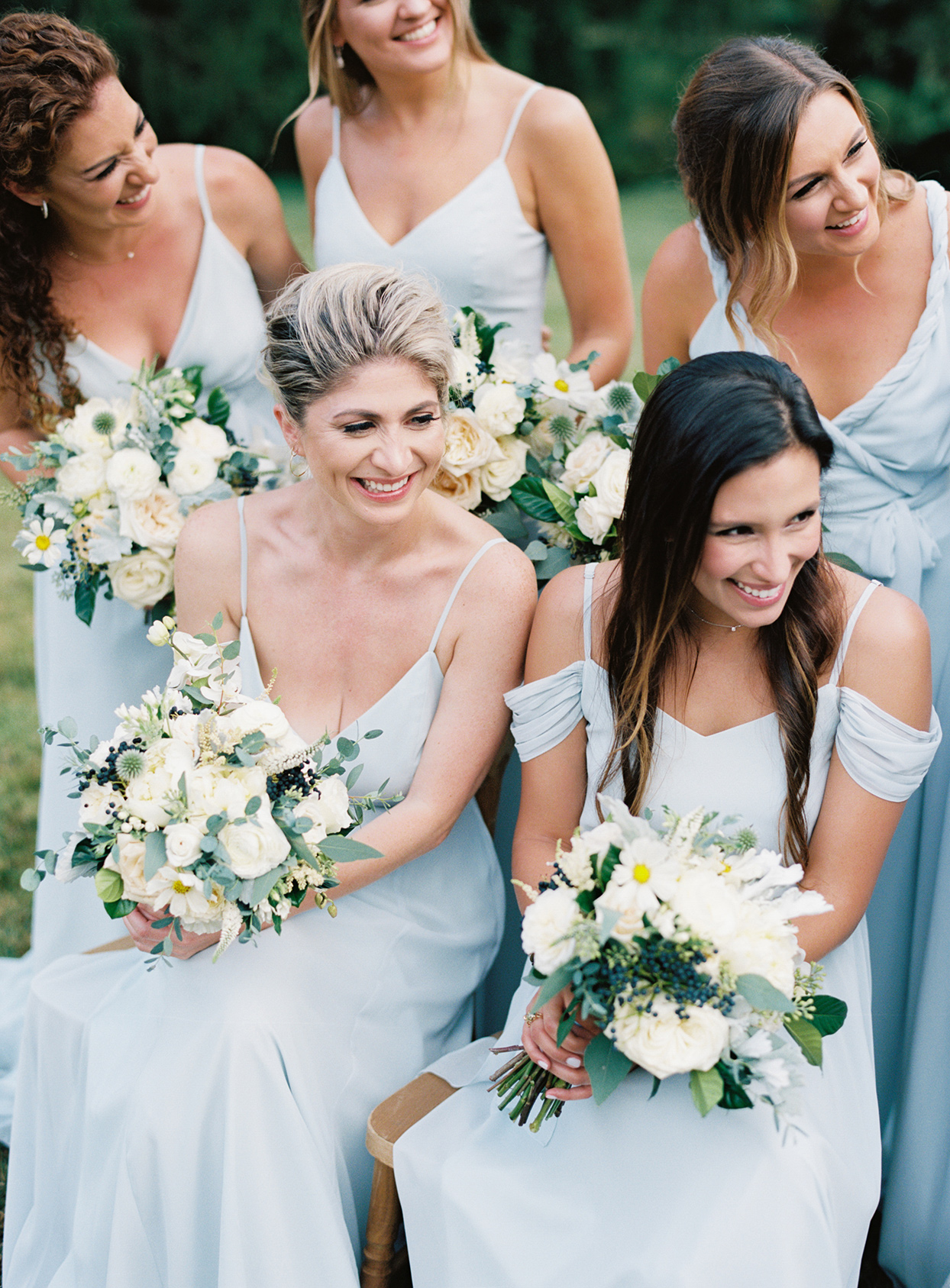 lauren chris wedding bridesmaids sitting in pastel blue dresses