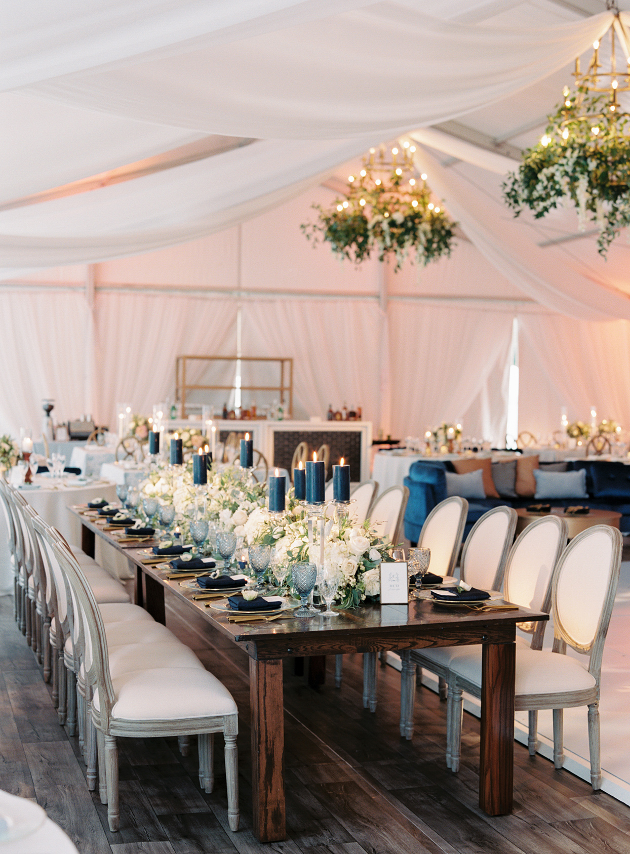 lauren chris wedding rustic long wooden table with white flowers and gold and blue place settings