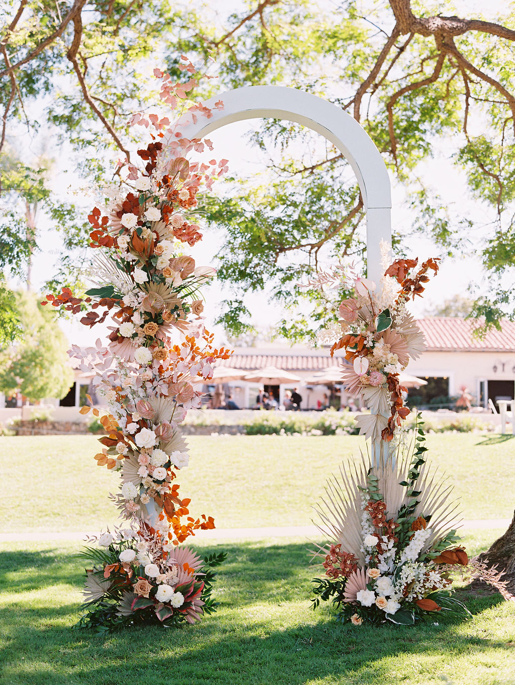 sara trisdan wedding white arch with warm tones floral decorations