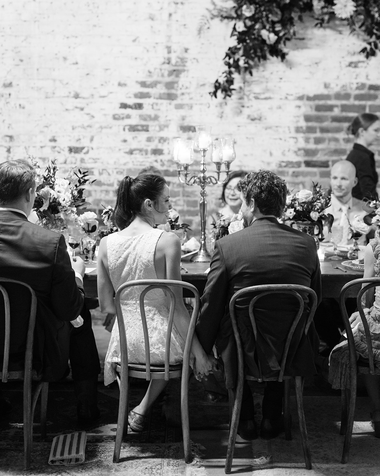 Wedding couple holding hands at dinner