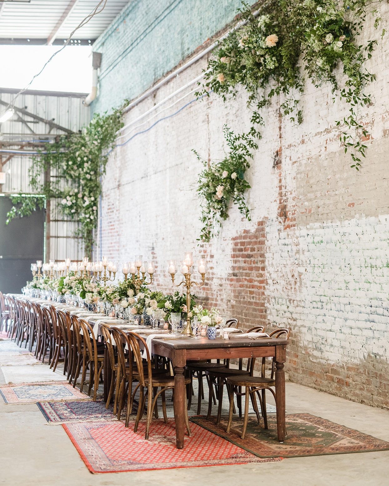 Long dining table with rugs and flowers