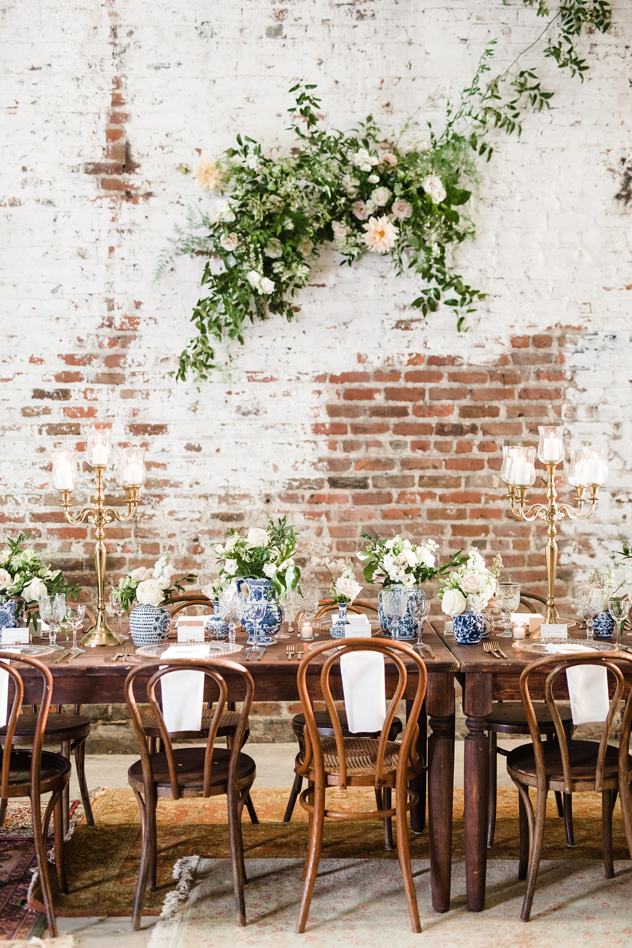 single long wooden table, brass candelabras and low bunches of flowers and foliage