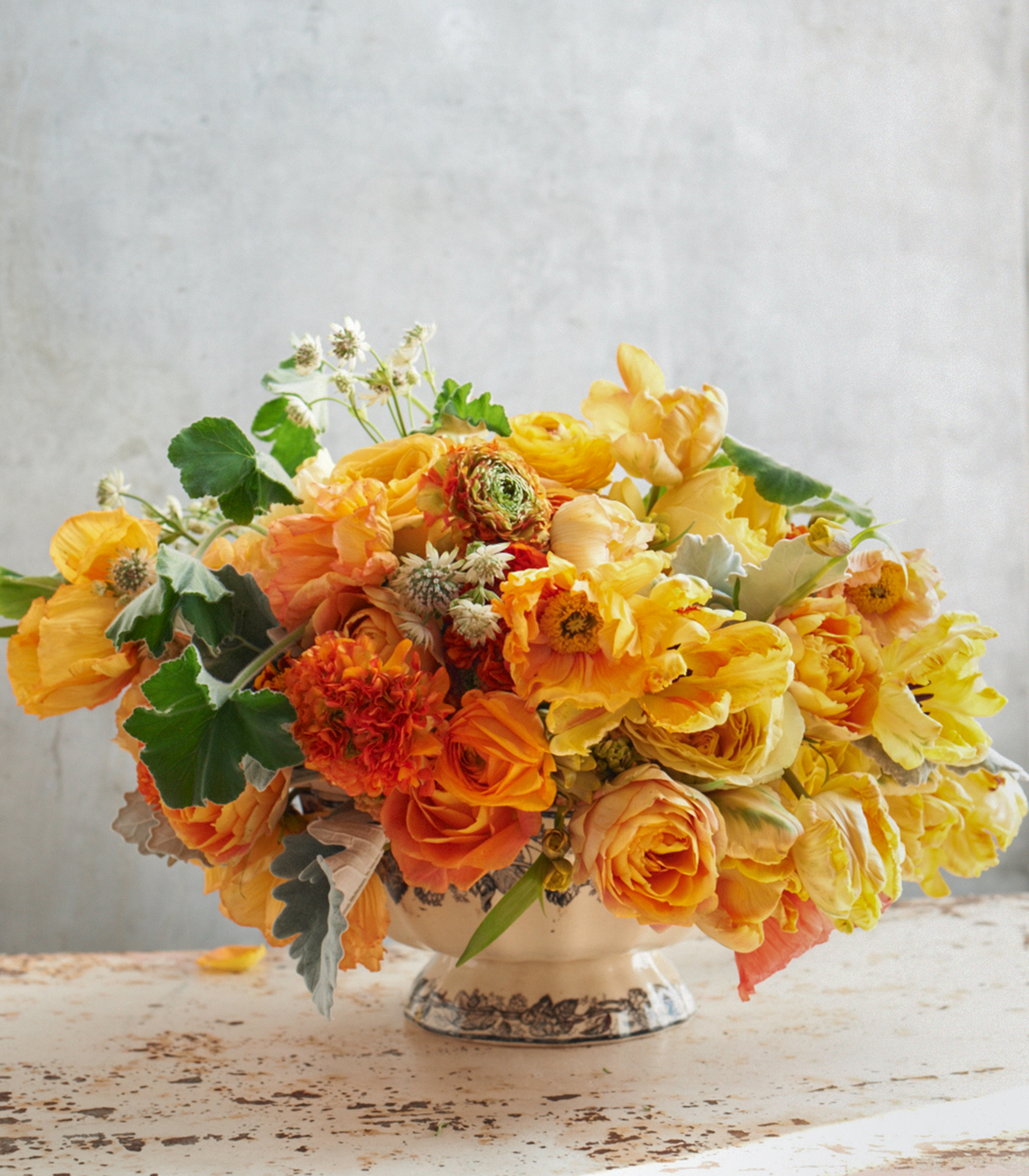 golden lilies roses ranunculus and poppies centerpiece