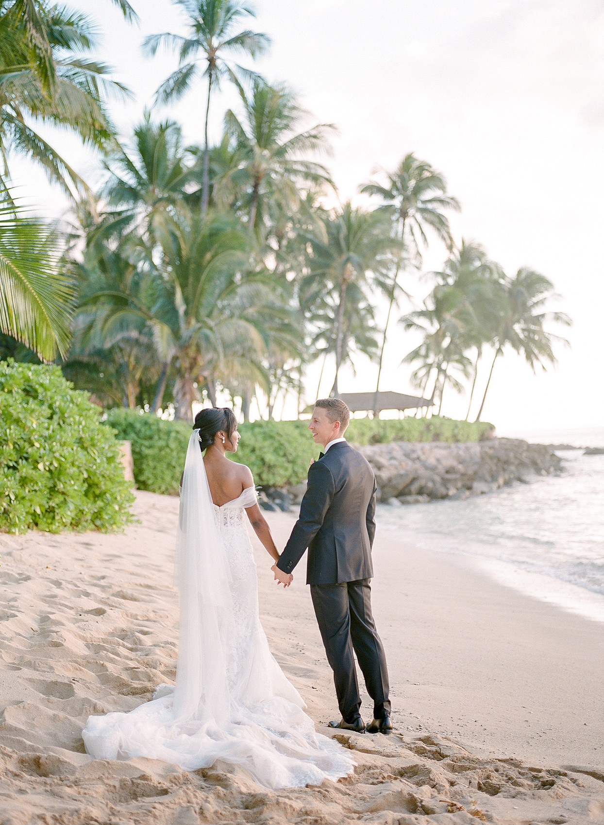couple holding hands on beach with palm tree backdrop