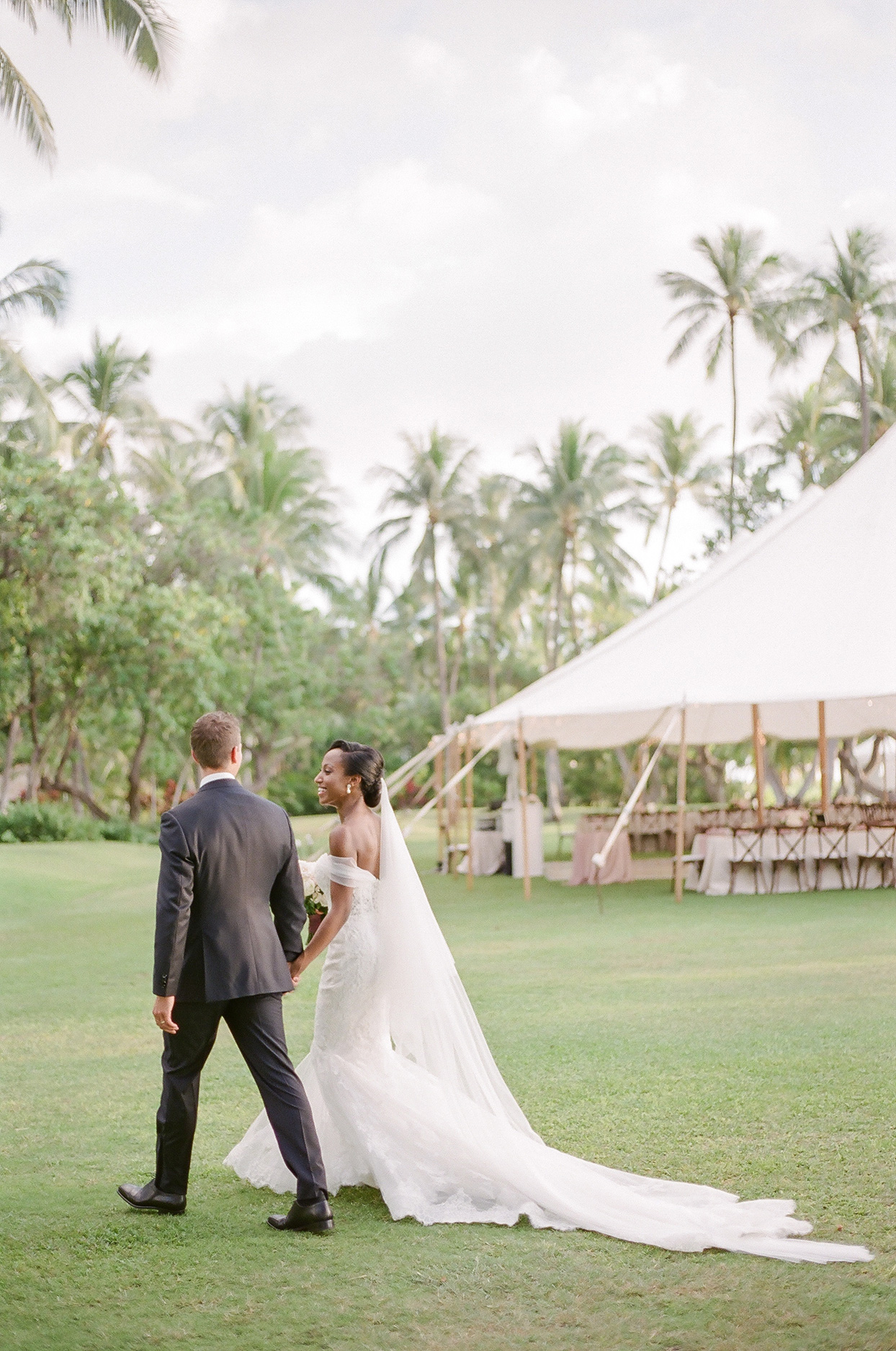 vanessa nathan wedding couple walking across grass with reception tent behind