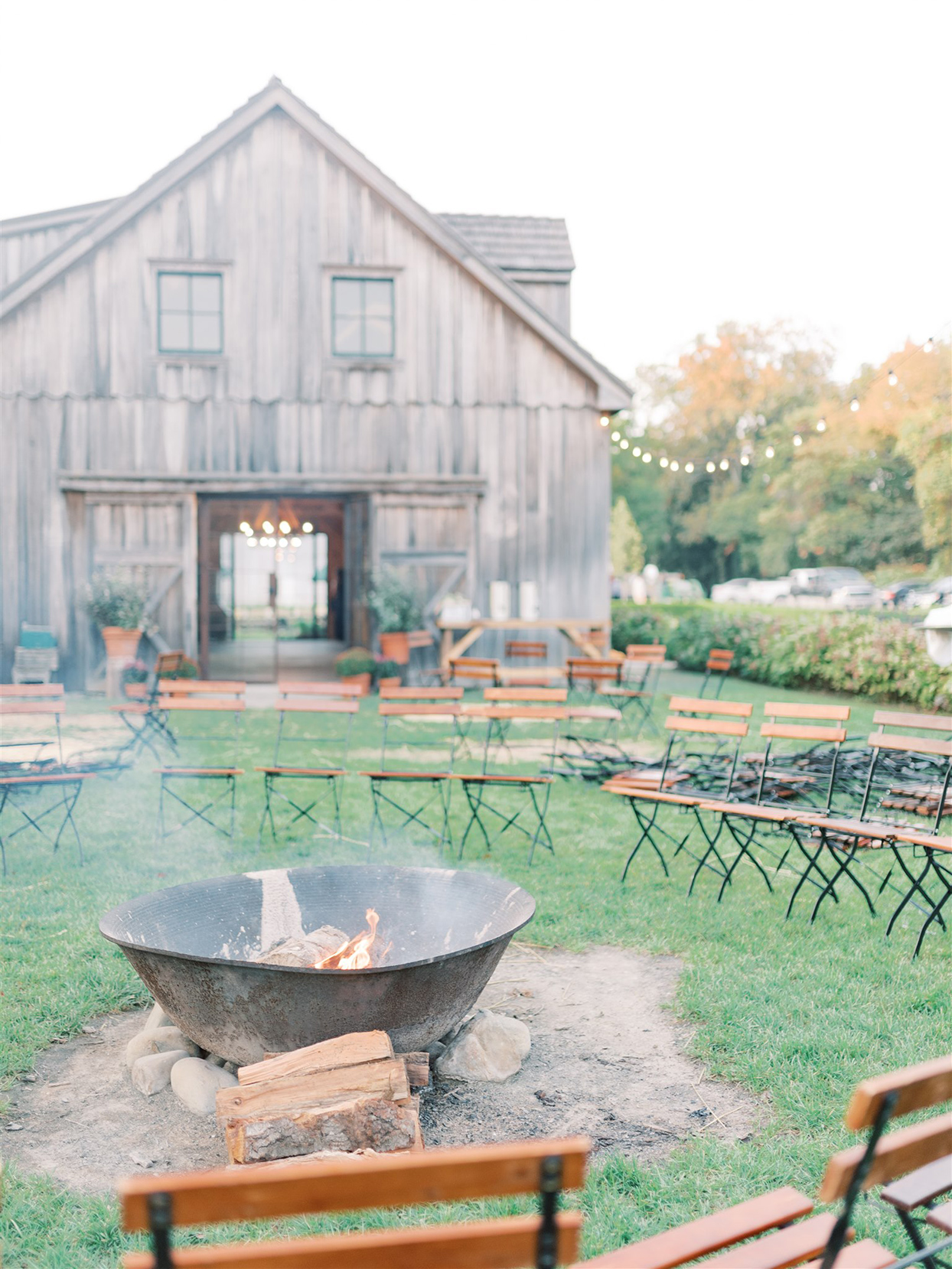 fire pit with chairs around it and barn in the background