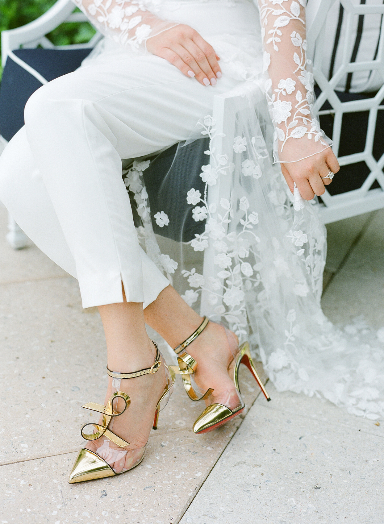 bride sitting in white romper and gold shoes during rehearsal dinner