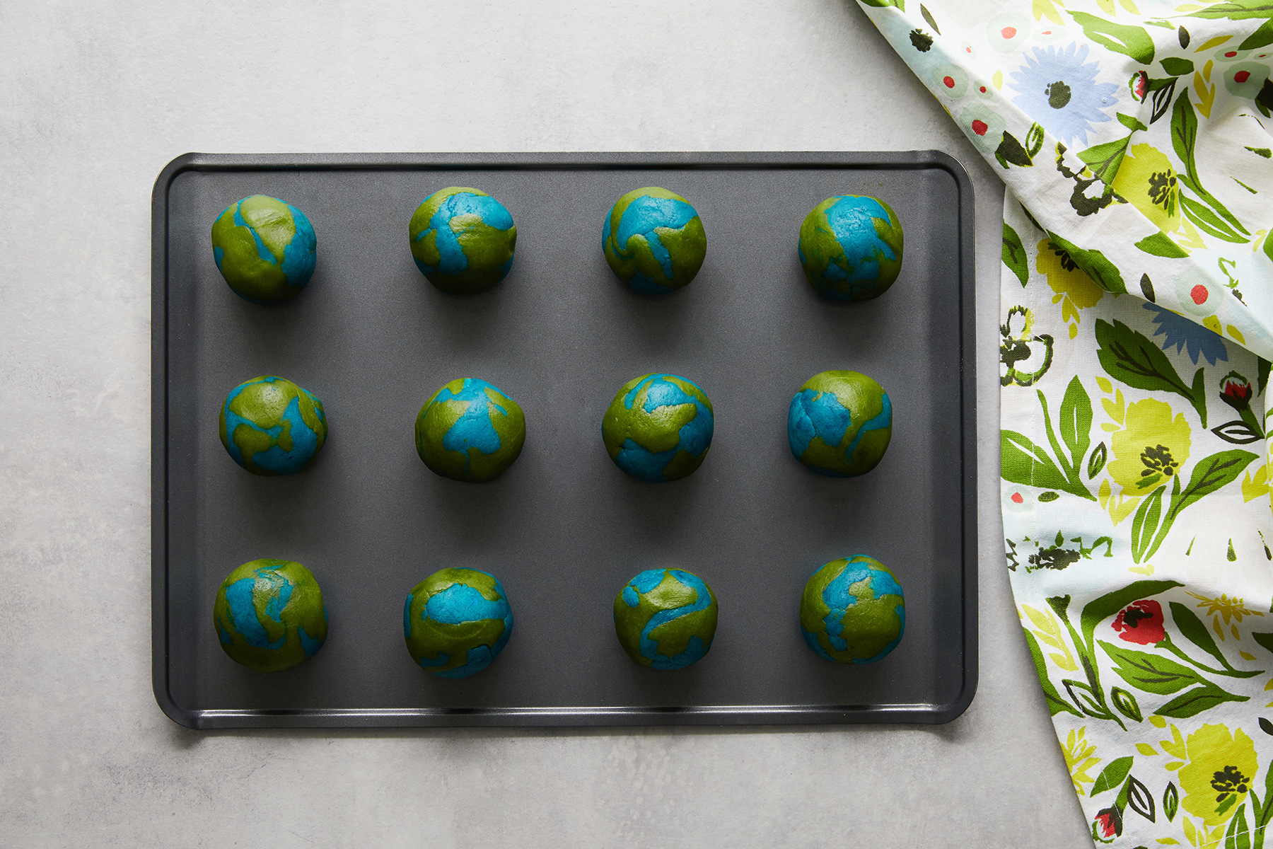 earth day cookies formed into balls on baking sheet