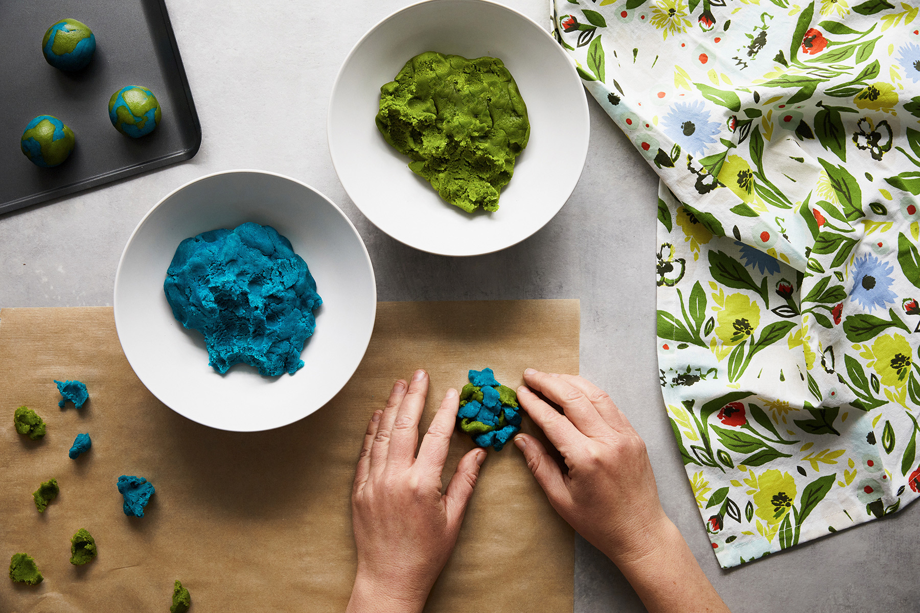 shaping blue and green dough into earth day cookies