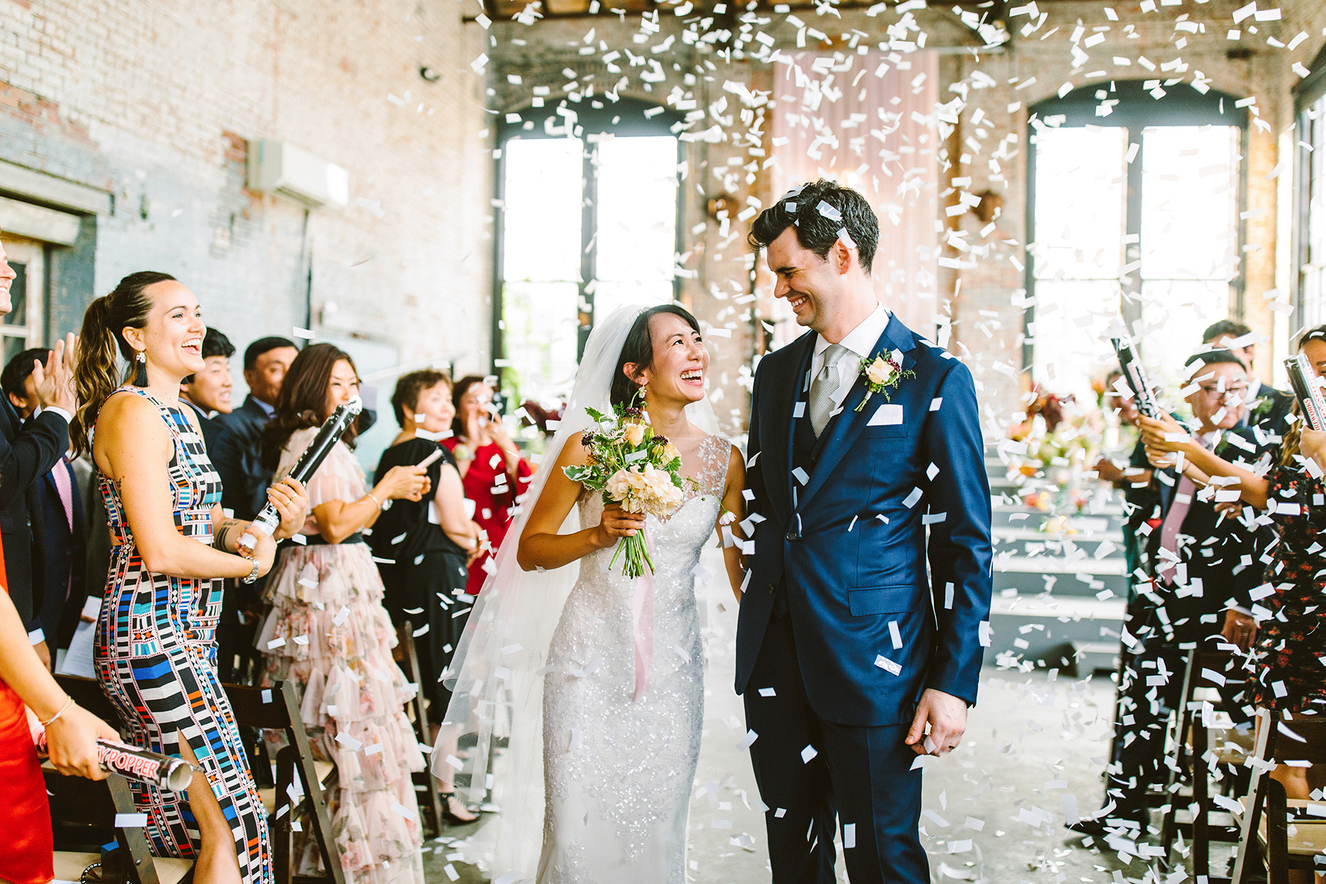 bride and groom exiting industrial wedding in shower of white confetti
