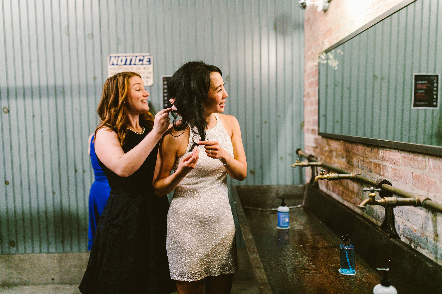 bride in short reception dress with bridesmaid getting hair fixed