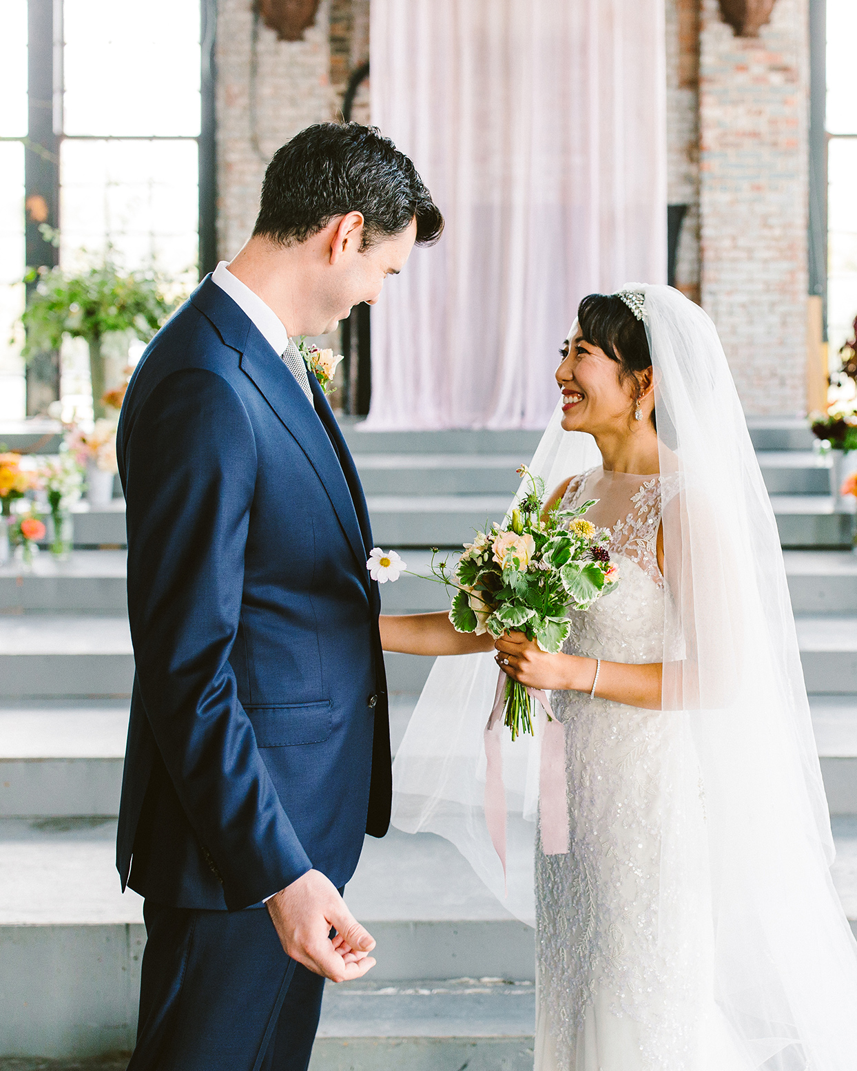 couple smiling during first look in industrial space