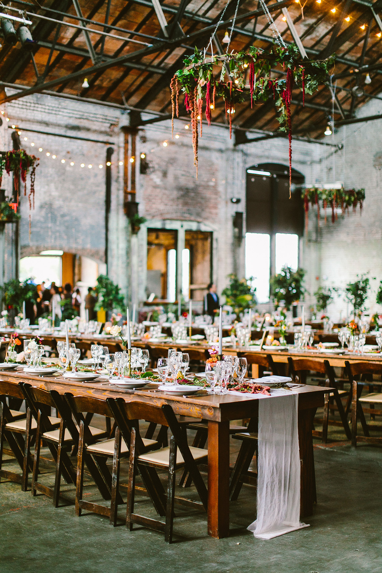 industrial rustic wedding reception set up with long wooden tables and hanging floral decorations
