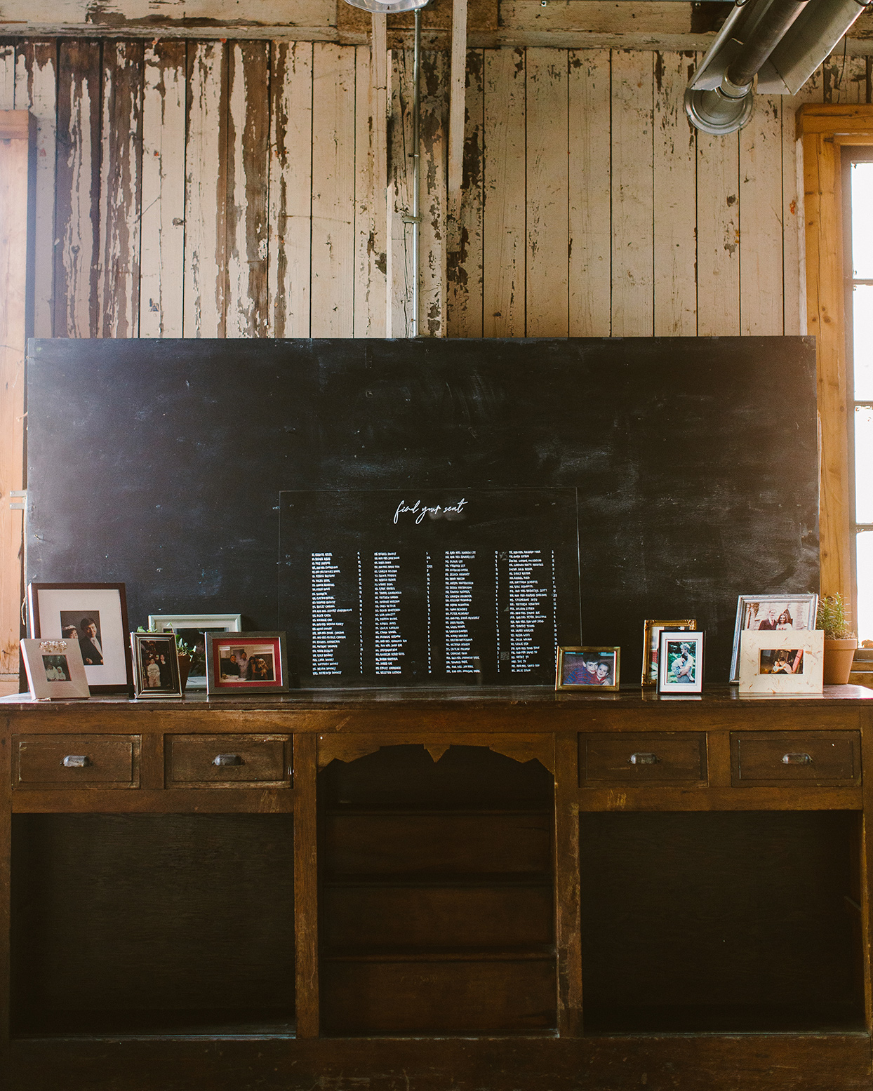 wedding seating chart propped up on antique wooden table with pictures of the couple