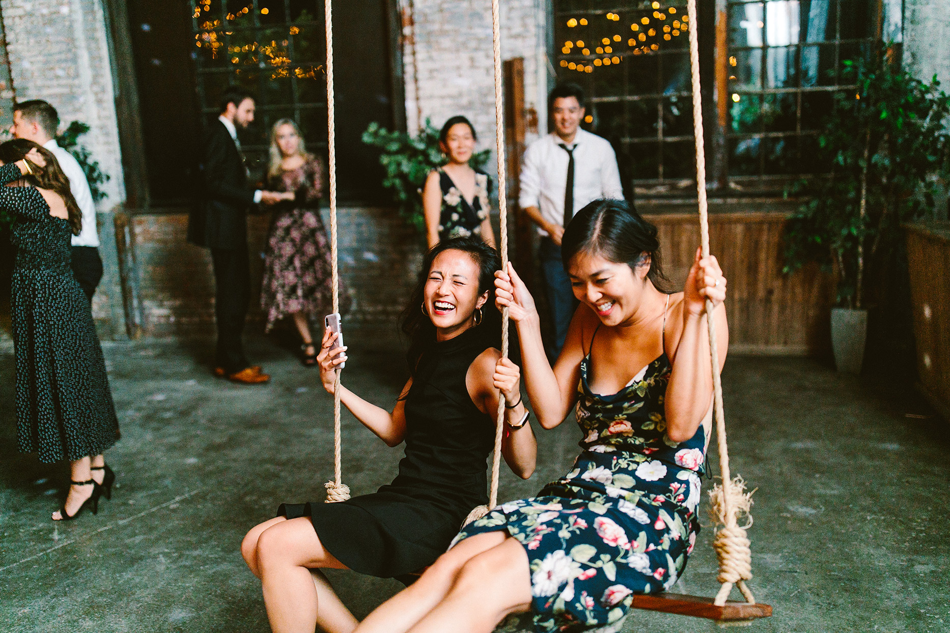 two guests laughing on swings at wedding reception