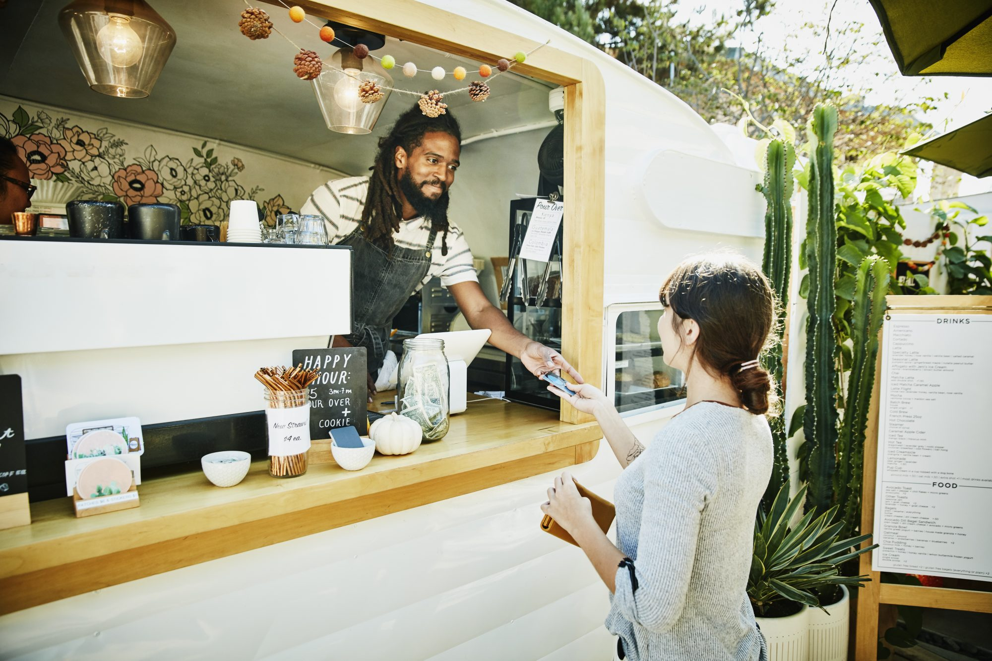 smiling food truck owner taking credit card for payment from customer