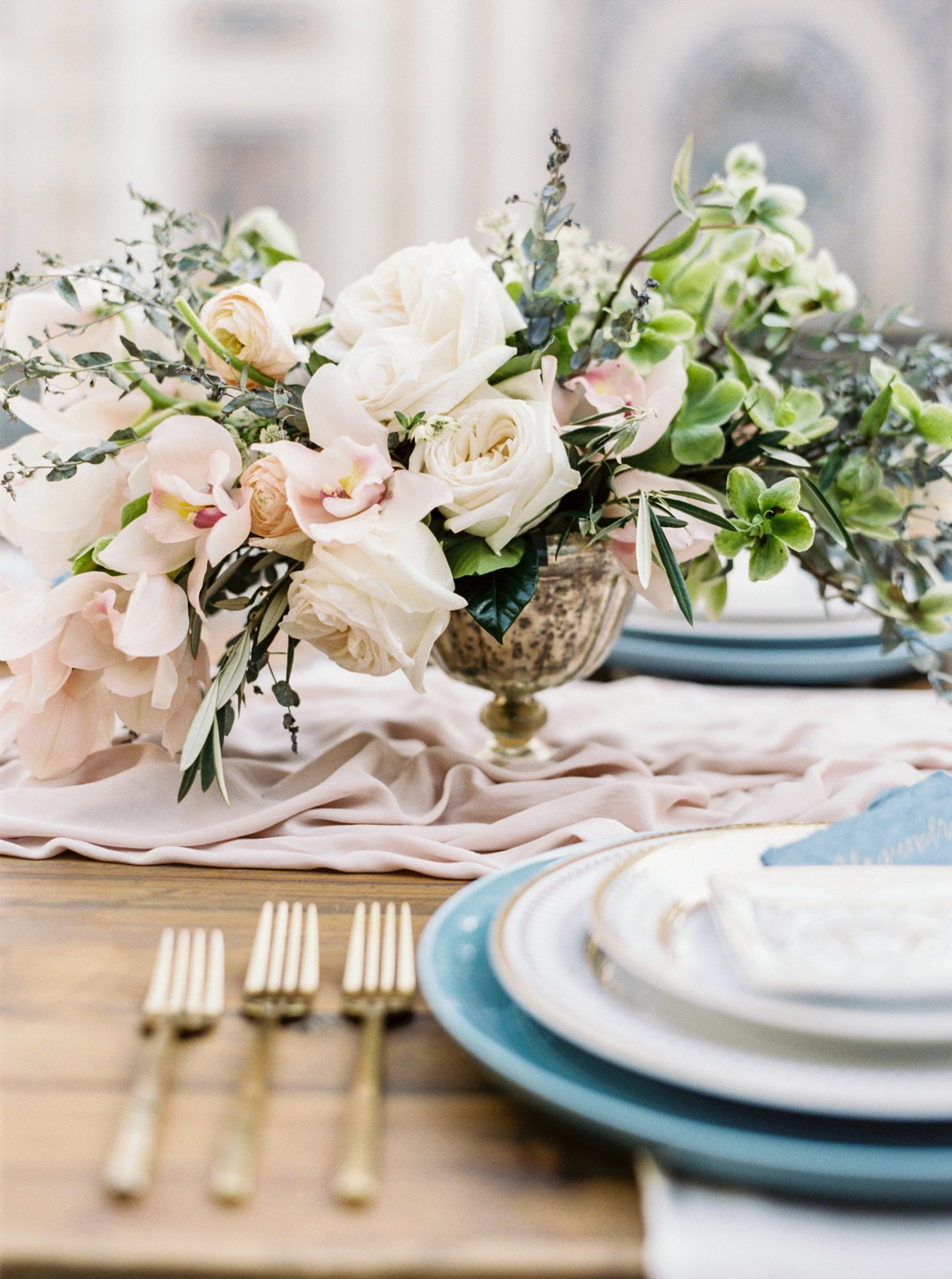 floral centerpieces in metallic vases on top of pale silk table runners