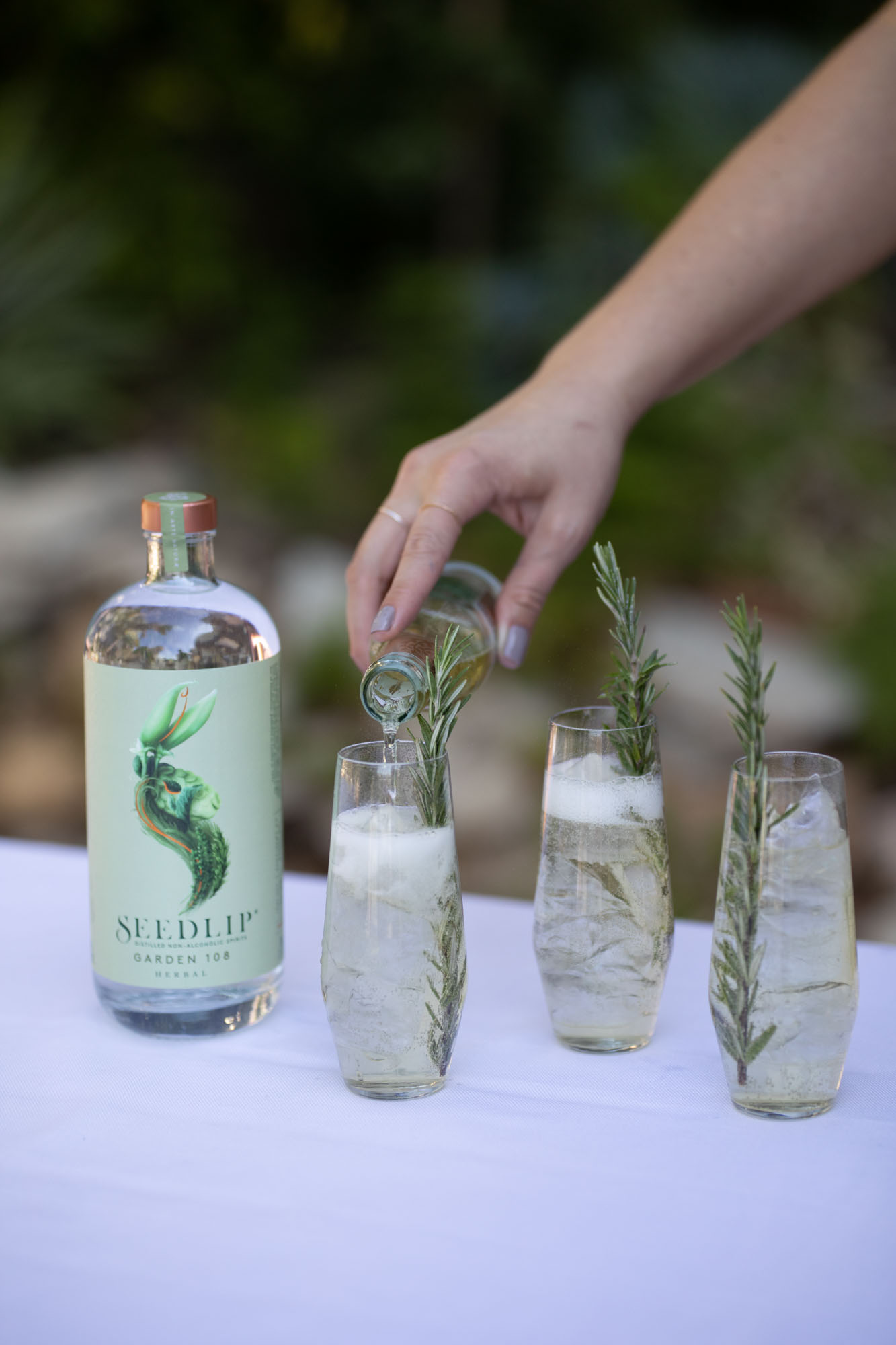 nonalcoholic cocktails with rosemary sprigs and bottle of Seedlip