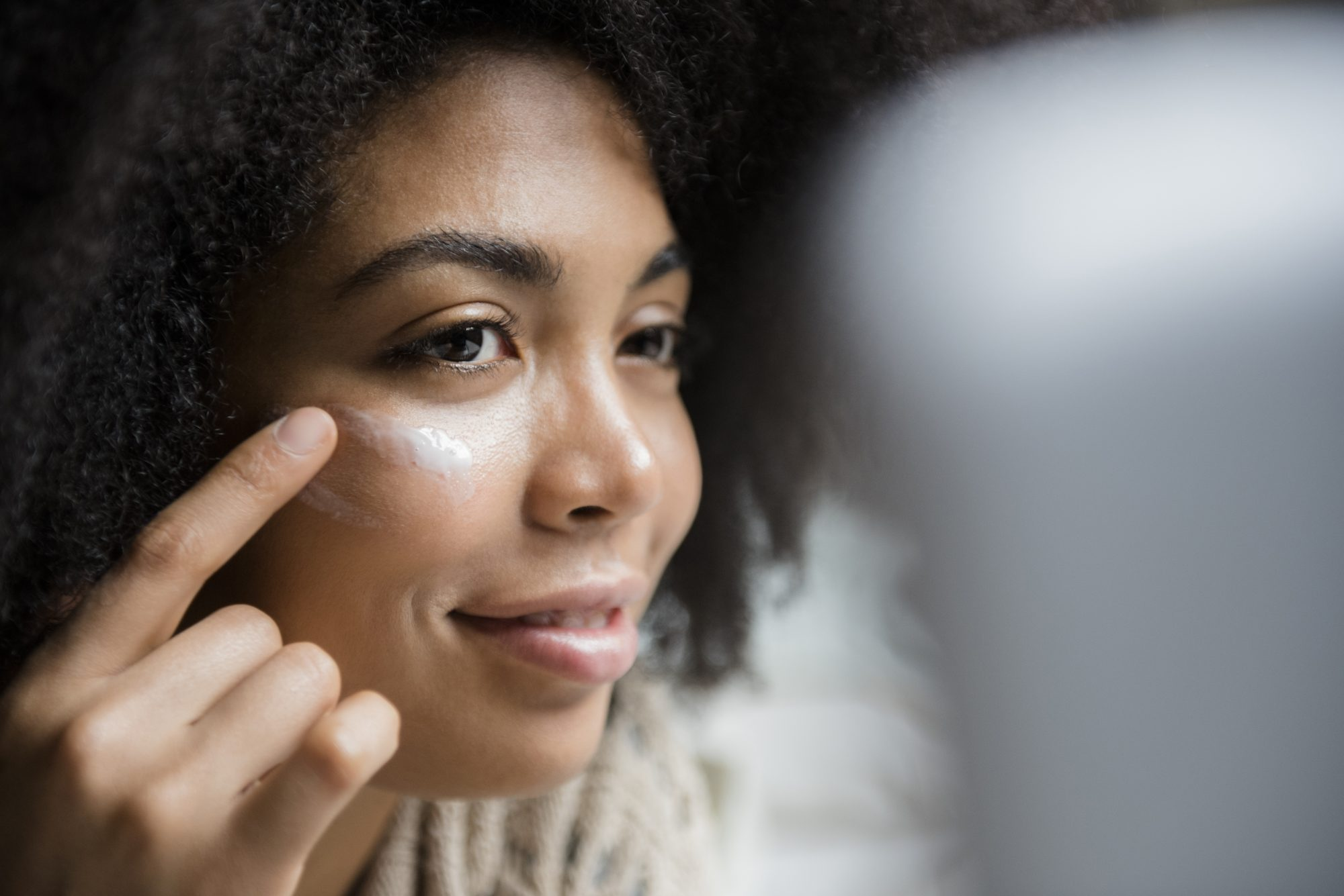 woman applying cream touching face in mirror