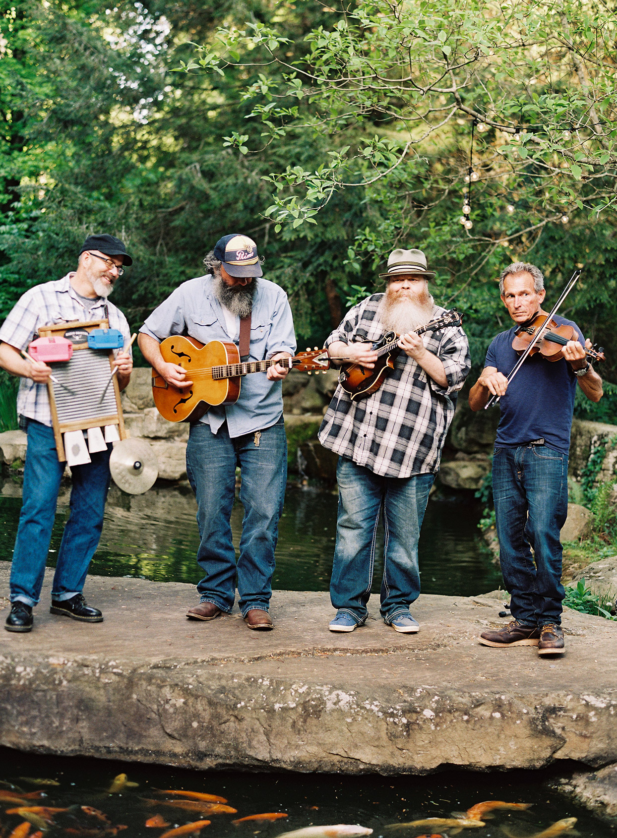 four men with bluegrass instruments playing for welcome party