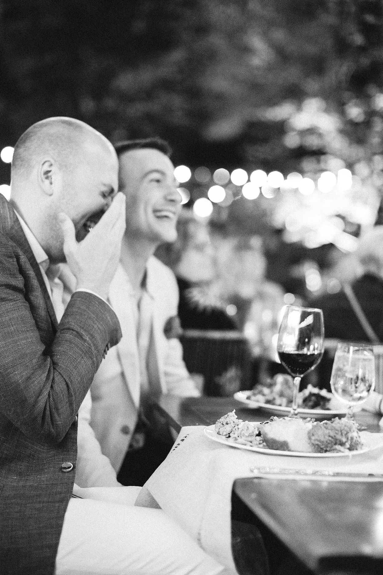 grooms laughing during speech at welcome party