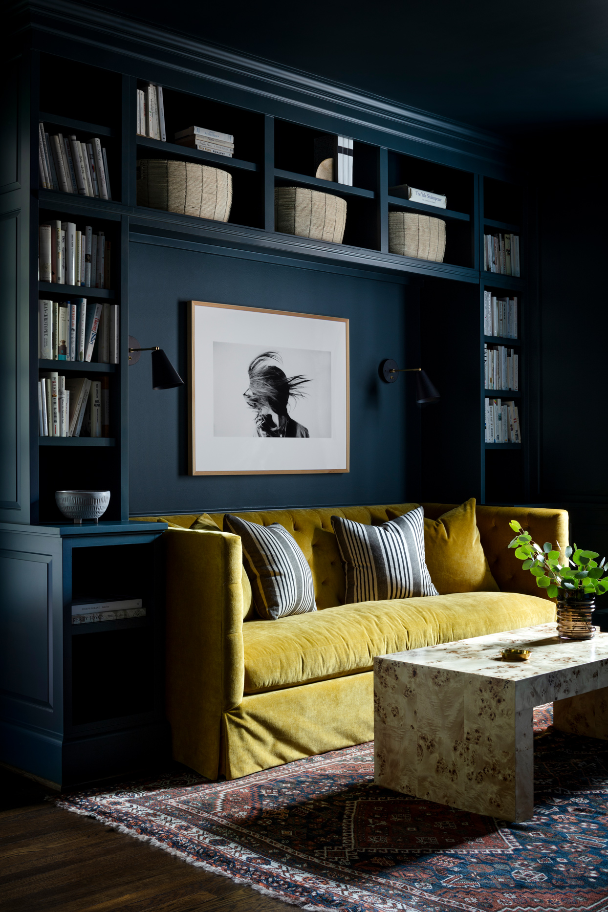 floor to ceiling navy blue wall shelving book case with yellow couch