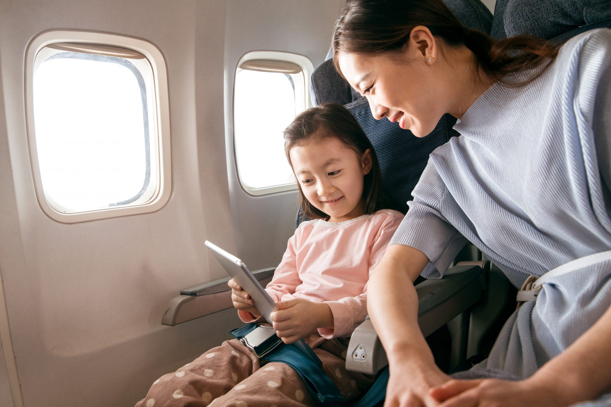 mother and daughter seated on a plane by the window