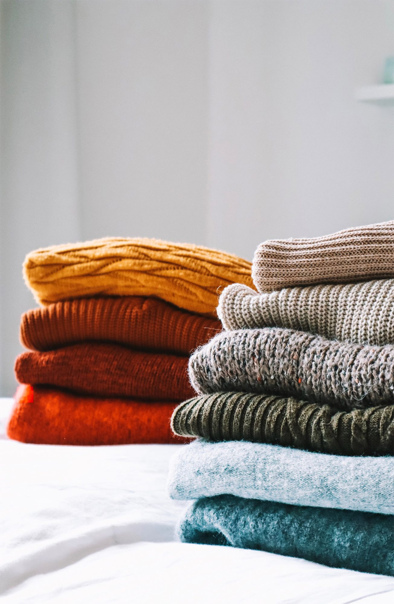 Close-Up Of Sweaters On Bed